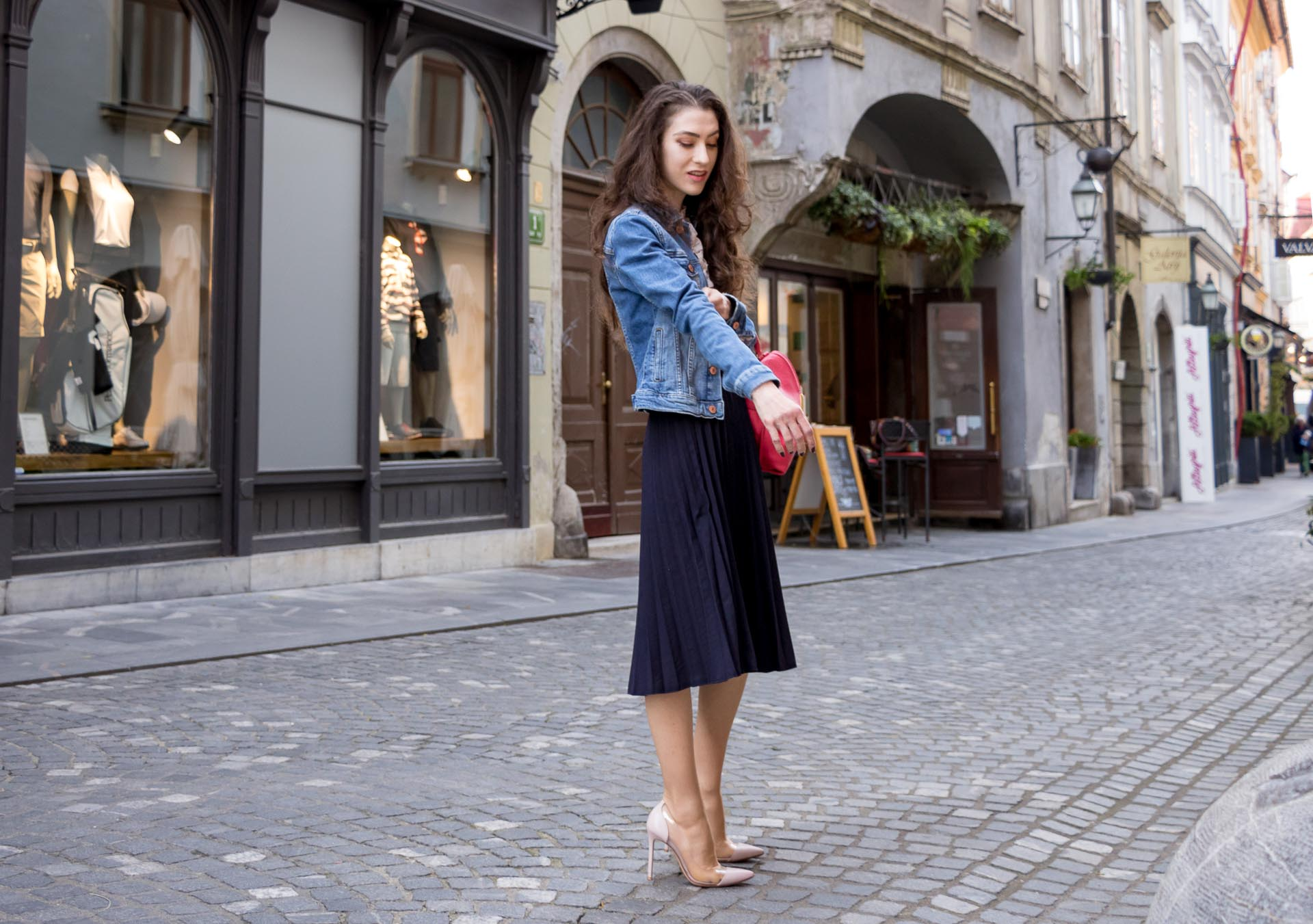 Veronika Lipar Fashion Blogger of Brunette from Wall Street dressed in H&M denim jacket, floral blouse, midi pleated skirt, Gianvito Rossi plexi pumps, pink top handle bag while rolling up the sleeves of denim jacket
