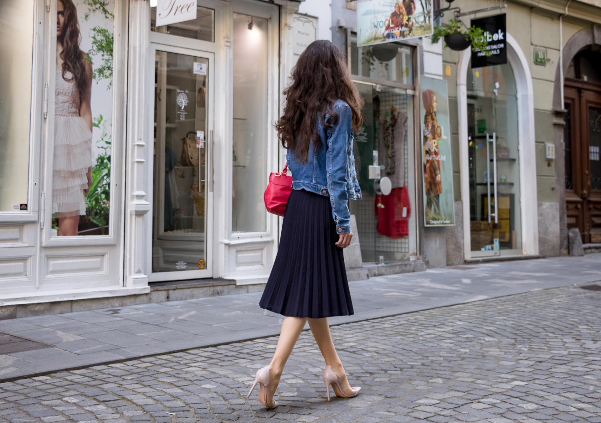 Veronika Lipar Fashion Blogger of Brunette from Wall Street wearing H&M denim jacket, floral blouse, midi pleated skirt, Gianvito Rossi plexi pumps, pink top handle bag while walking on the street in Ljubljana