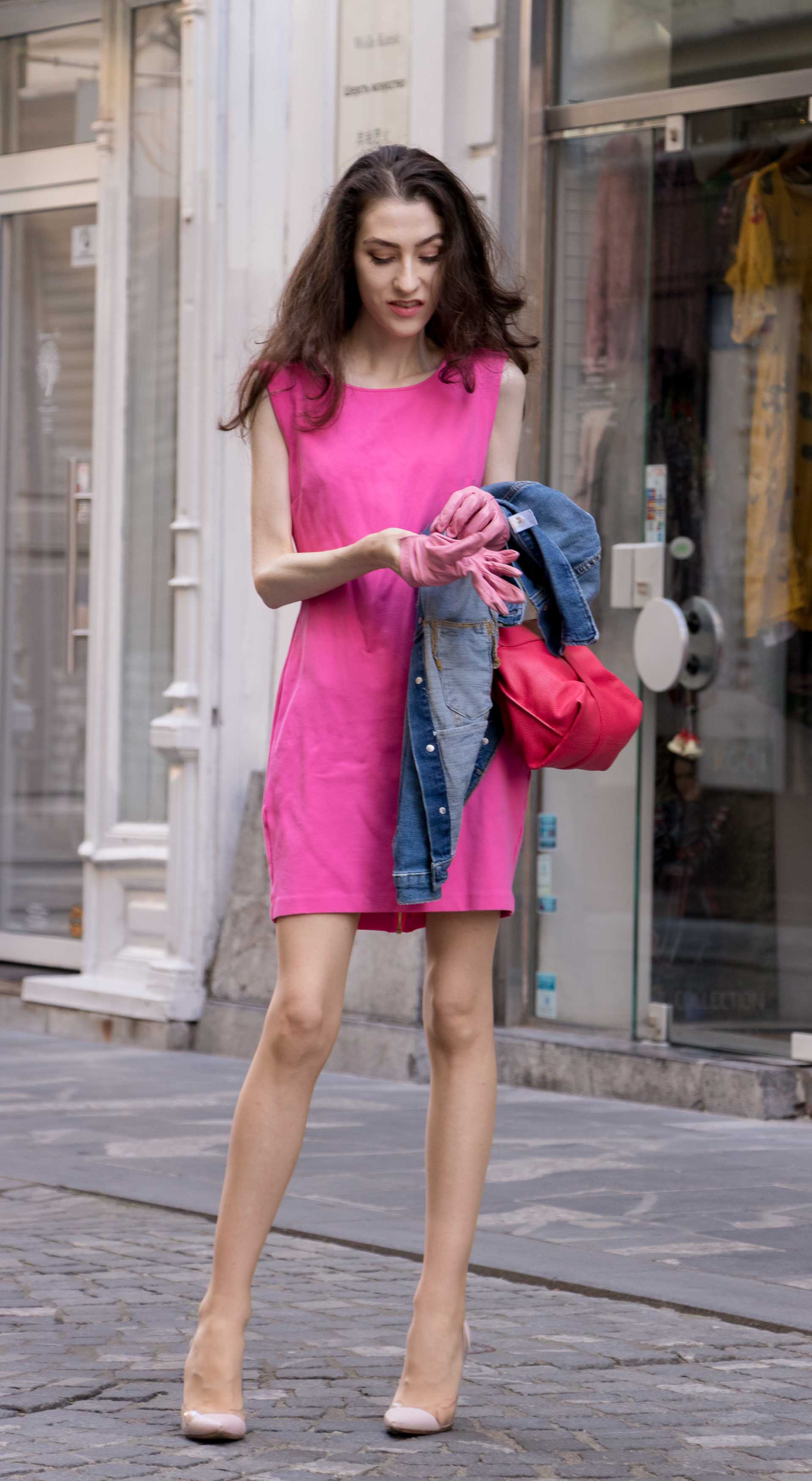 Veronika Lipar Fashion Blogger of Brunette from Wall Street wearing H&M denim jacket, pink bodycon dress, blush Gianvito Rossi plexi pumps, pink Forzieri gloves, See by Chloé pink top handle bag, Adam Selman x Le Specs white cat eye Lolita sunglasses while standing on the street in Ljubljana