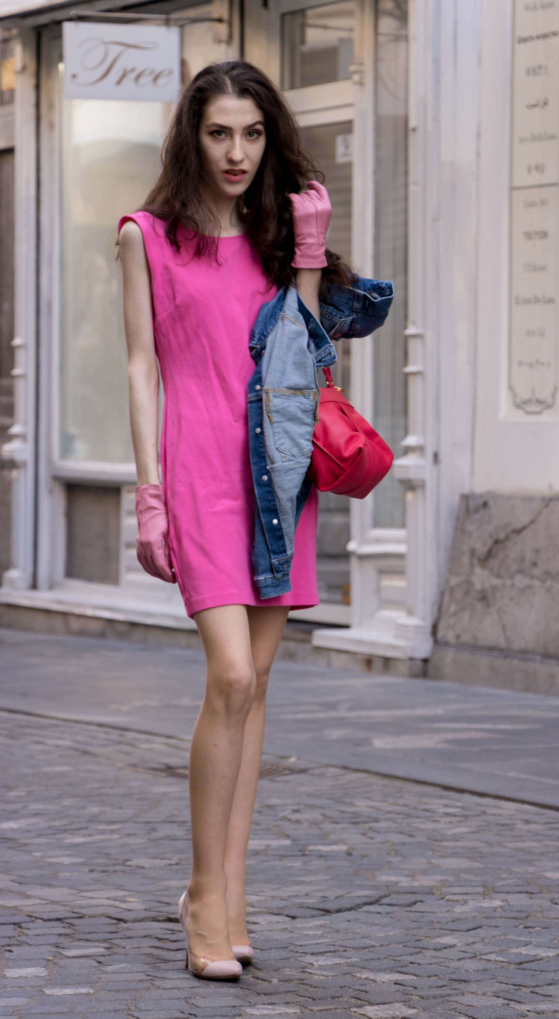 Veronika Lipar Fashion Blogger of Brunette from Wall Street wearing H&M denim jacket, pink short dress, blush Gianvito Rossi plexi pumps, pink Forzieri gloves, See by Chloé pink top handle bag, Adam Selman x Le Specs white cat eye Lolita sunglasses while standing on the street in Ljubljana