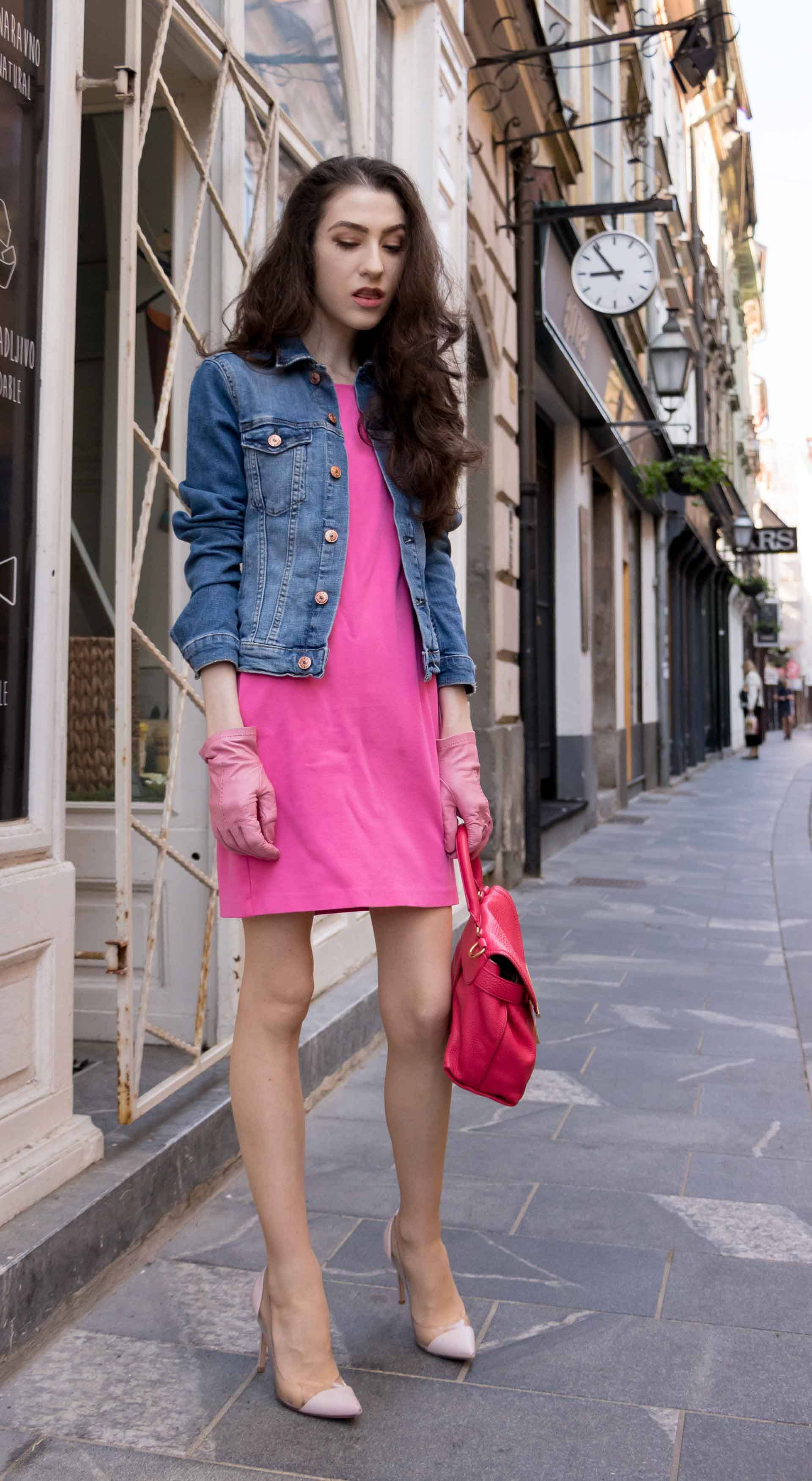 Veronika Lipar Fashion Blogger of Brunette from Wall Street wearing H&M denim jacket, pink cocktail dress, blush Gianvito Rossi plexi pumps, pink Forzieri gloves, See by Chloé pink top handle bag, Adam Selman x Le Specs white cat eye Lolita sunglasses while standing on the street in Ljubljana