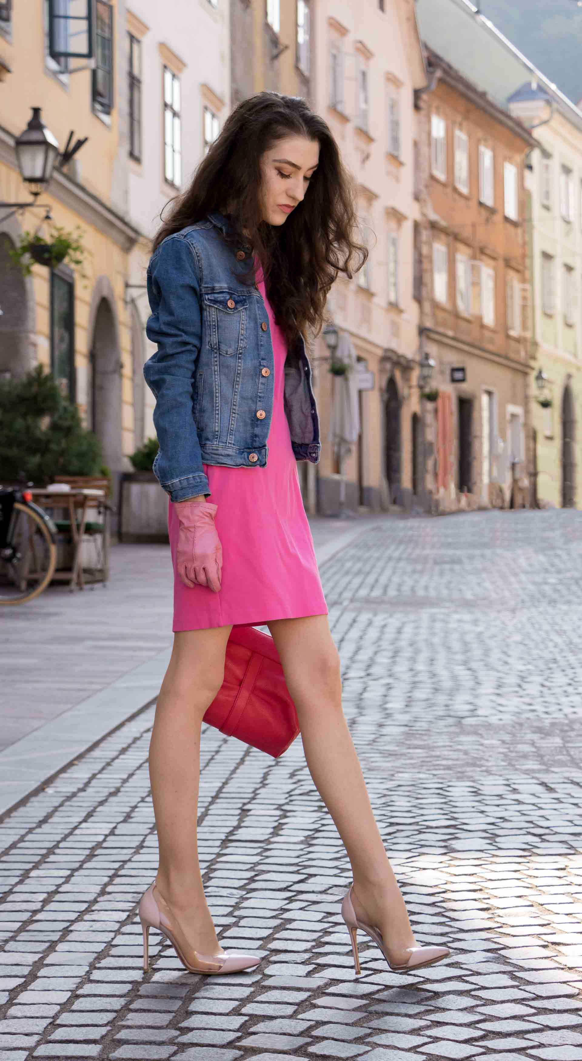 Veronika Lipar Fashion Blogger of Brunette from Wall Street dressed in H&M denim jacket, pink cocktail dress, blush Gianvito Rossi plexi pumps, pink Forzieri gloves, See by Chloé pink top handle bag, Adam Selman x Le Specs white cat eye Lolita sunglasses while walking on the street in Ljubljana