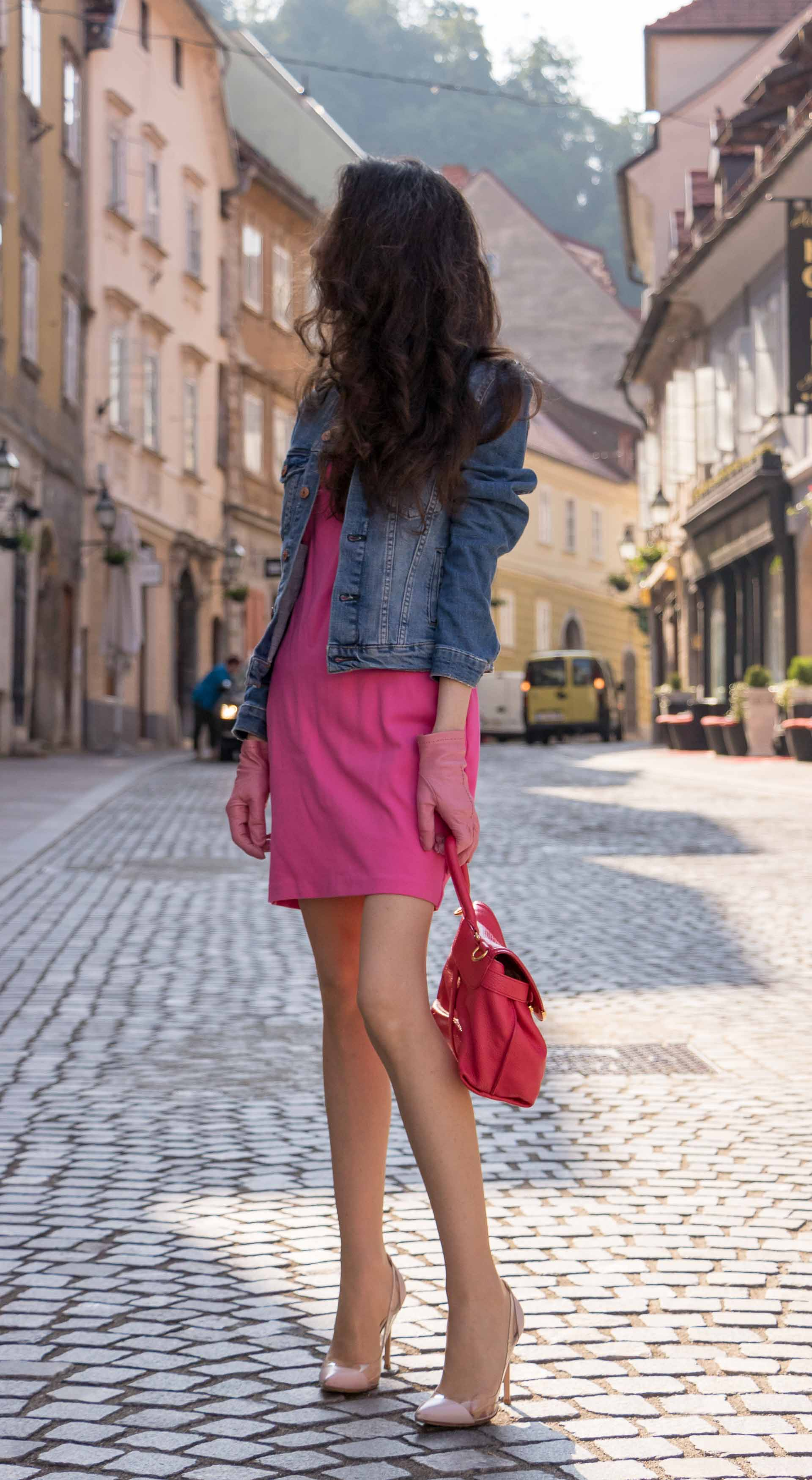 Veronika Lipar Fashion Blogger of Brunette from Wall Street dressed in H&M denim jacket, pink short dress, blush Gianvito Rossi plexi pumps, pink Forzieri gloves, See by Chloé pink top handle bag, Adam Selman x Le Specs white cat eye Lolita sunglasses while standing on the street in Ljubljana
