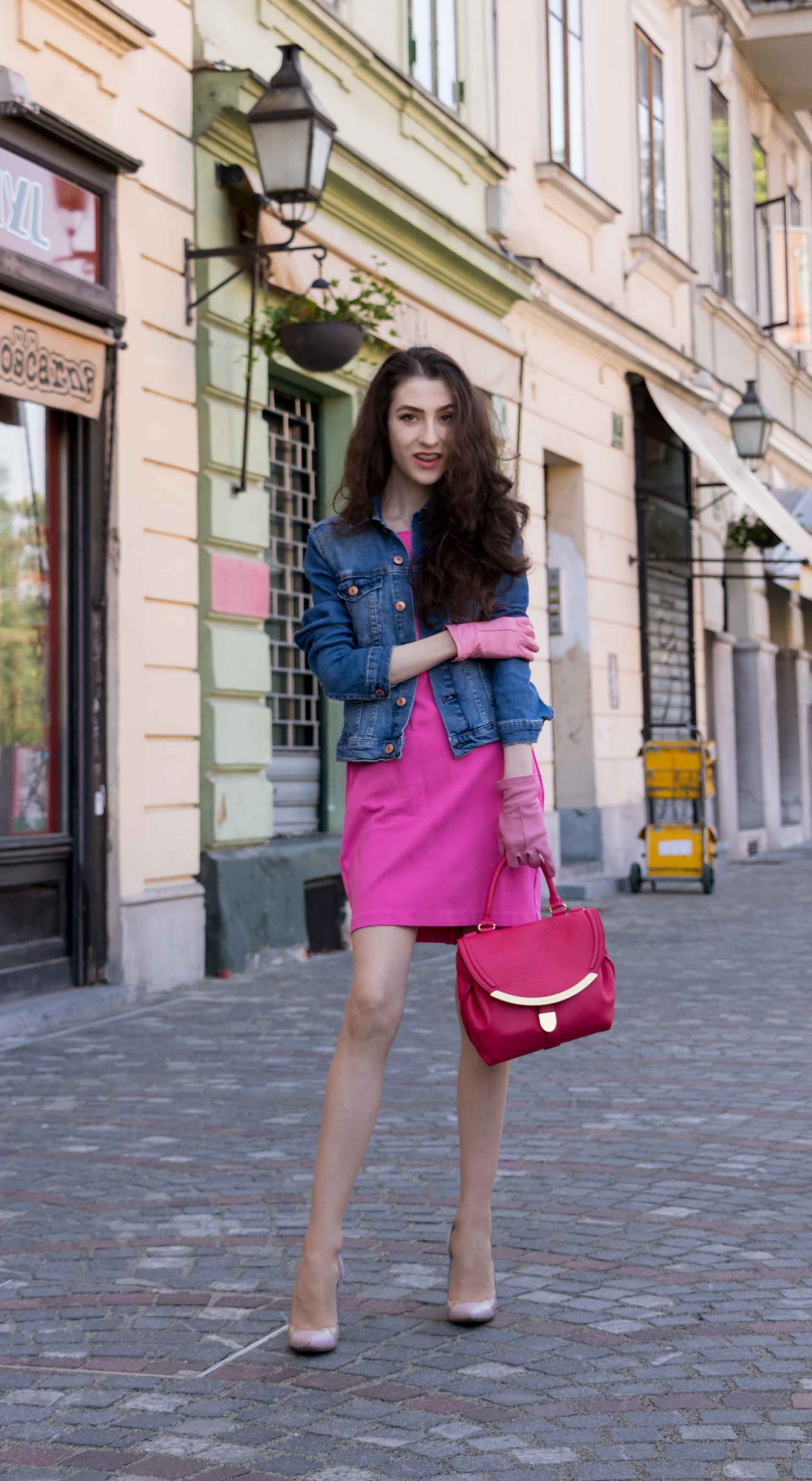 Veronika Lipar Fashion Blogger of Brunette from Wall Street wearing H&M denim jacket, pink shift cady dress, blush Gianvito Rossi plexi pumps, pink Forzieri gloves, See by Chloé pink top handle bag, Adam Selman x Le Specs white cat eye Lolita sunglasses while standing on the street in Ljubljana