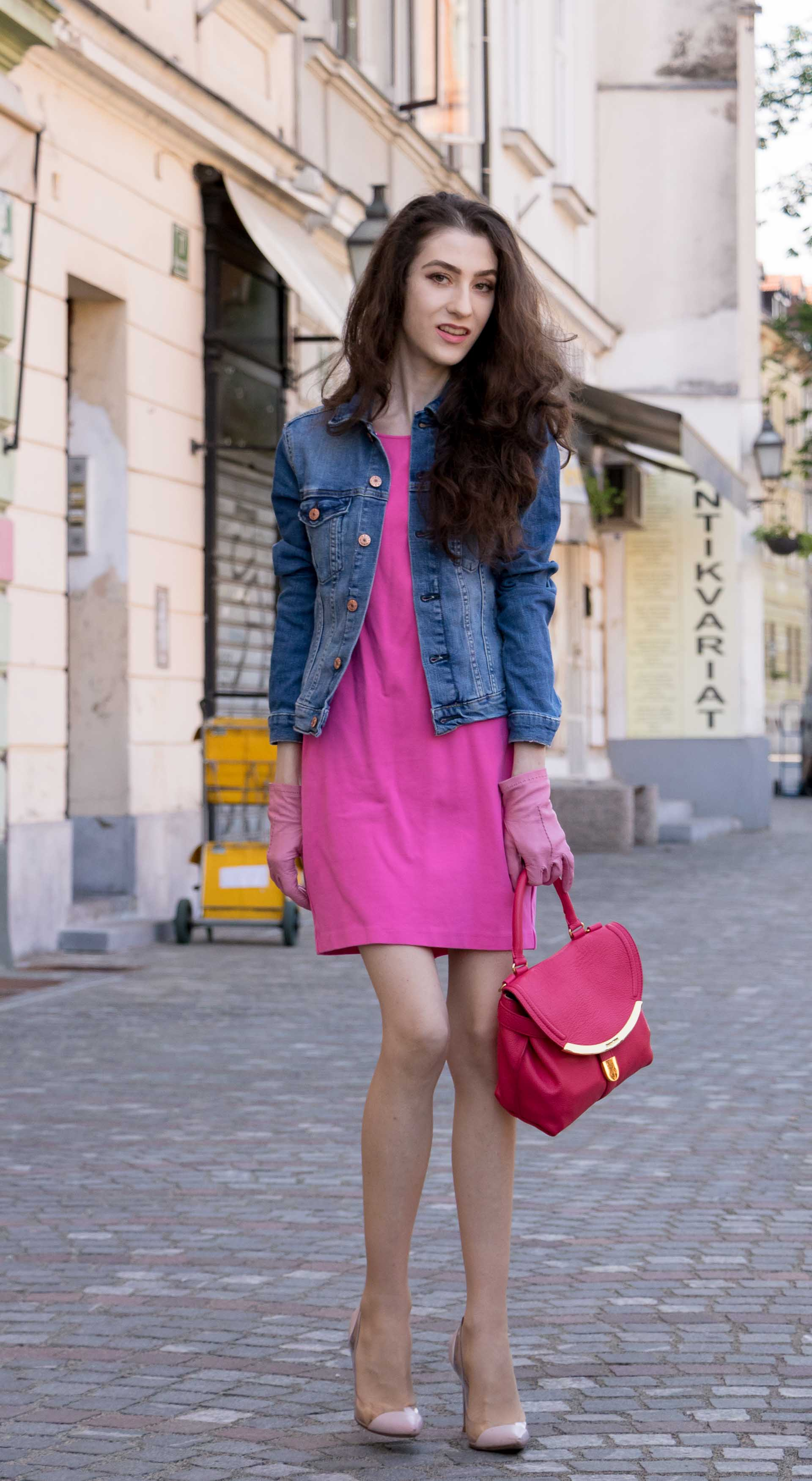 Veronika Lipar Fashion Blogger of Brunette from Wall Street dressed in H&M denim jacket, pink shift cady dress, blush Gianvito Rossi plexi pumps, pink Forzieri gloves, See by Chloé pink top handle bag, Adam Selman x Le Specs white cat eye Lolita sunglasses while standing on the street in Ljubljana