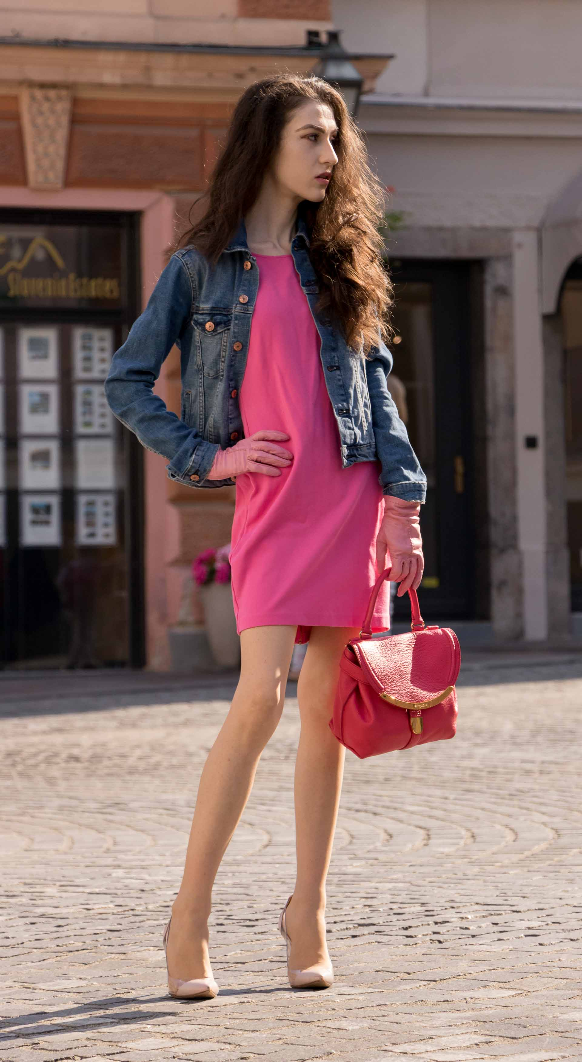 Veronika Lipar Fashion Blogger of Brunette from Wall Street dressed in H&M denim jacket, pink shift cady dress, blush Gianvito Rossi plexi pumps, pink Forzieri gloves, See by Chloé pink top handle bag, Adam Selman x Le Specs white cat eye Lolita sunglasses on the street in Ljubljana