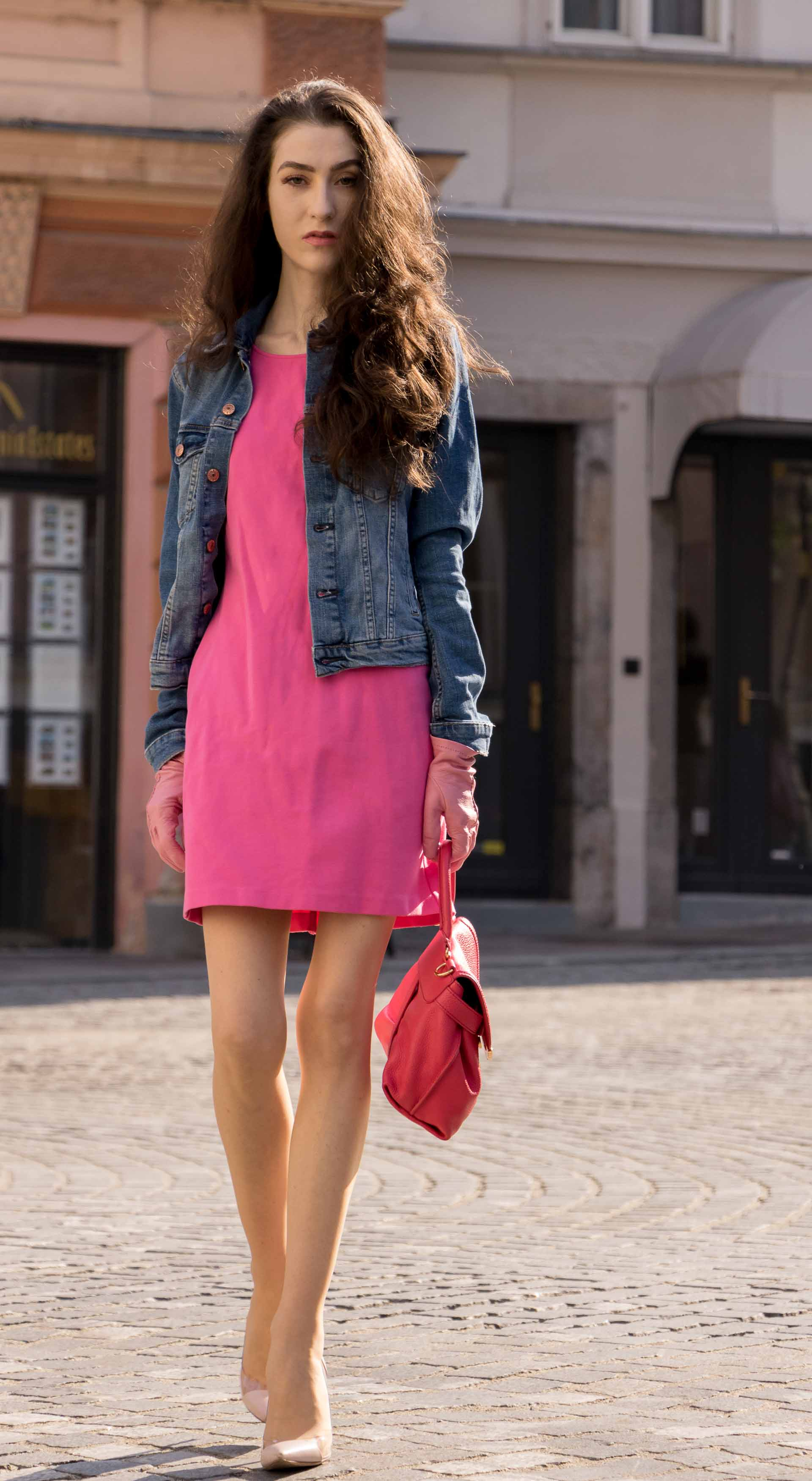 Veronika Lipar Fashion Blogger of Brunette from Wall Street dressed in H&M denim jacket, pink bodycon dress, blush Gianvito Rossi plexi pumps, pink Forzieri gloves, See by Chloé pink top handle bag, Adam Selman x Le Specs white cat eye Lolita sunglasses while walking on the street in Ljubljana