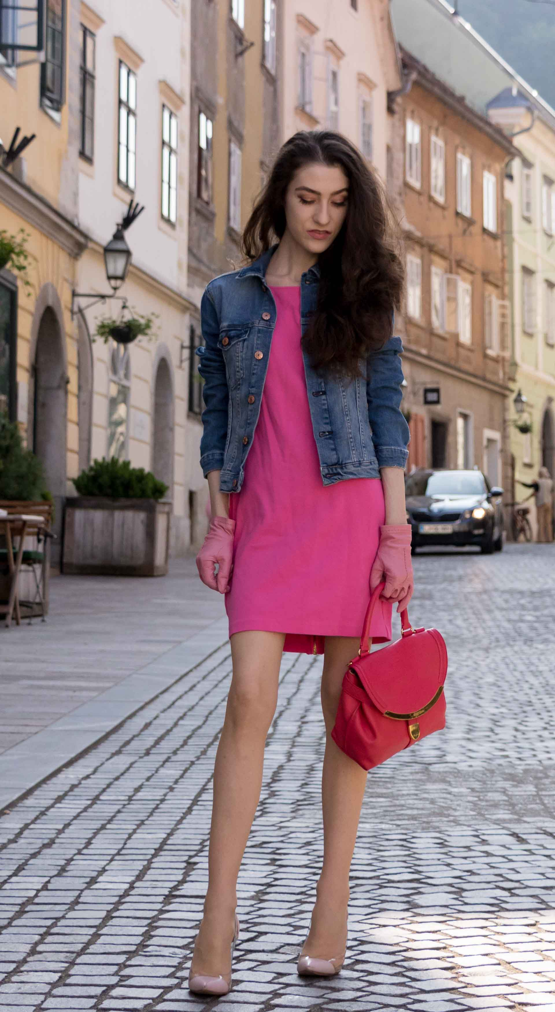 Veronika Lipar Fashion Blogger of Brunette from Wall Street dressed in H&M denim jacket, pink summer dress, blush Gianvito Rossi plexi pumps, pink Forzieri gloves, See by Chloé pink top handle bag, Adam Selman x Le Specs white cat eye Lolita sunglasses while standing on the street in Ljubljana