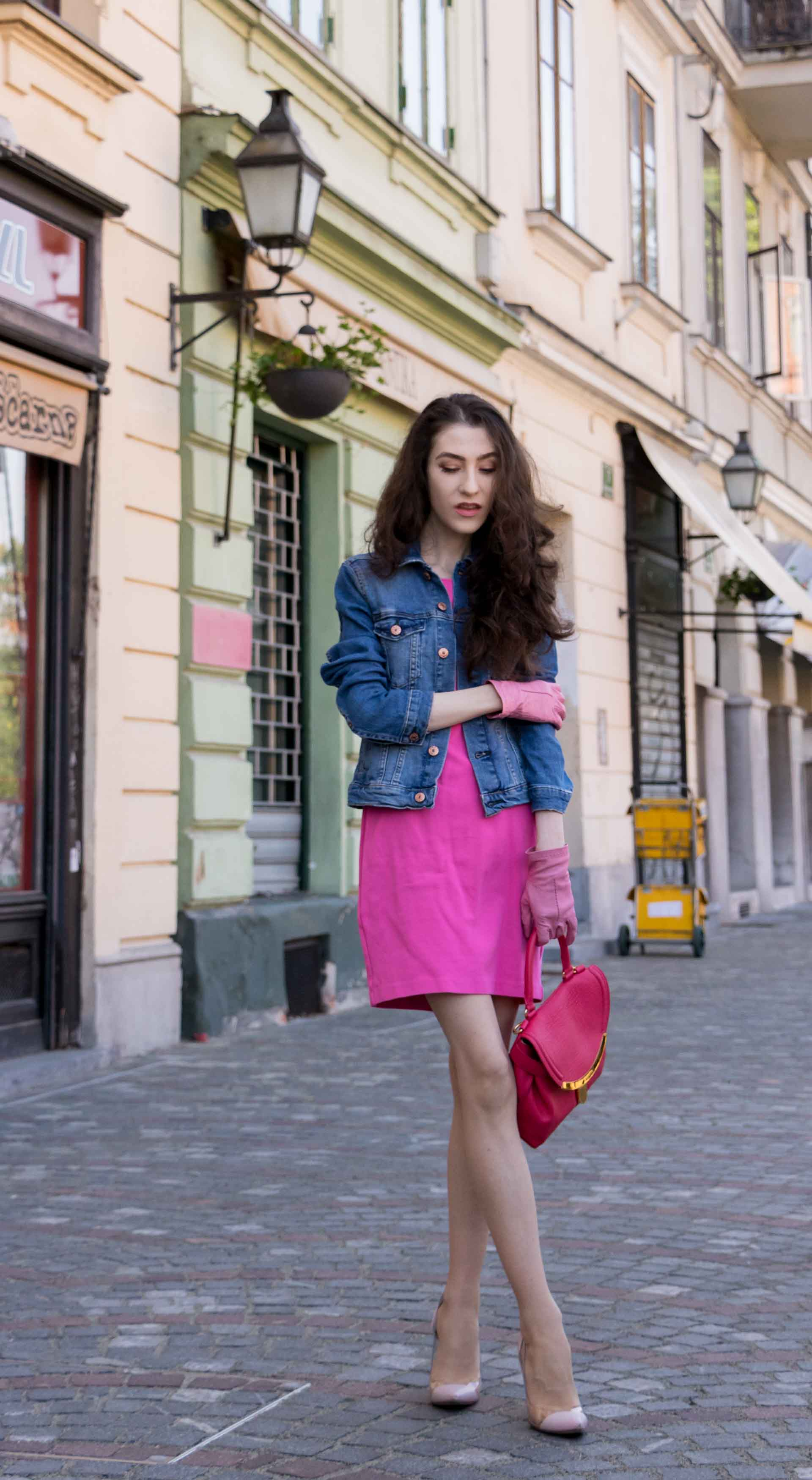 Veronika Lipar Fashion Blogger of Brunette from Wall Street dressed in H&M denim jacket, pink cocktail dress, blush Gianvito Rossi plexi pumps, pink Forzieri gloves, See by Chloé pink top handle bag, Adam Selman x Le Specs white cat eye Lolita sunglasses while standing on the street in Ljubljana