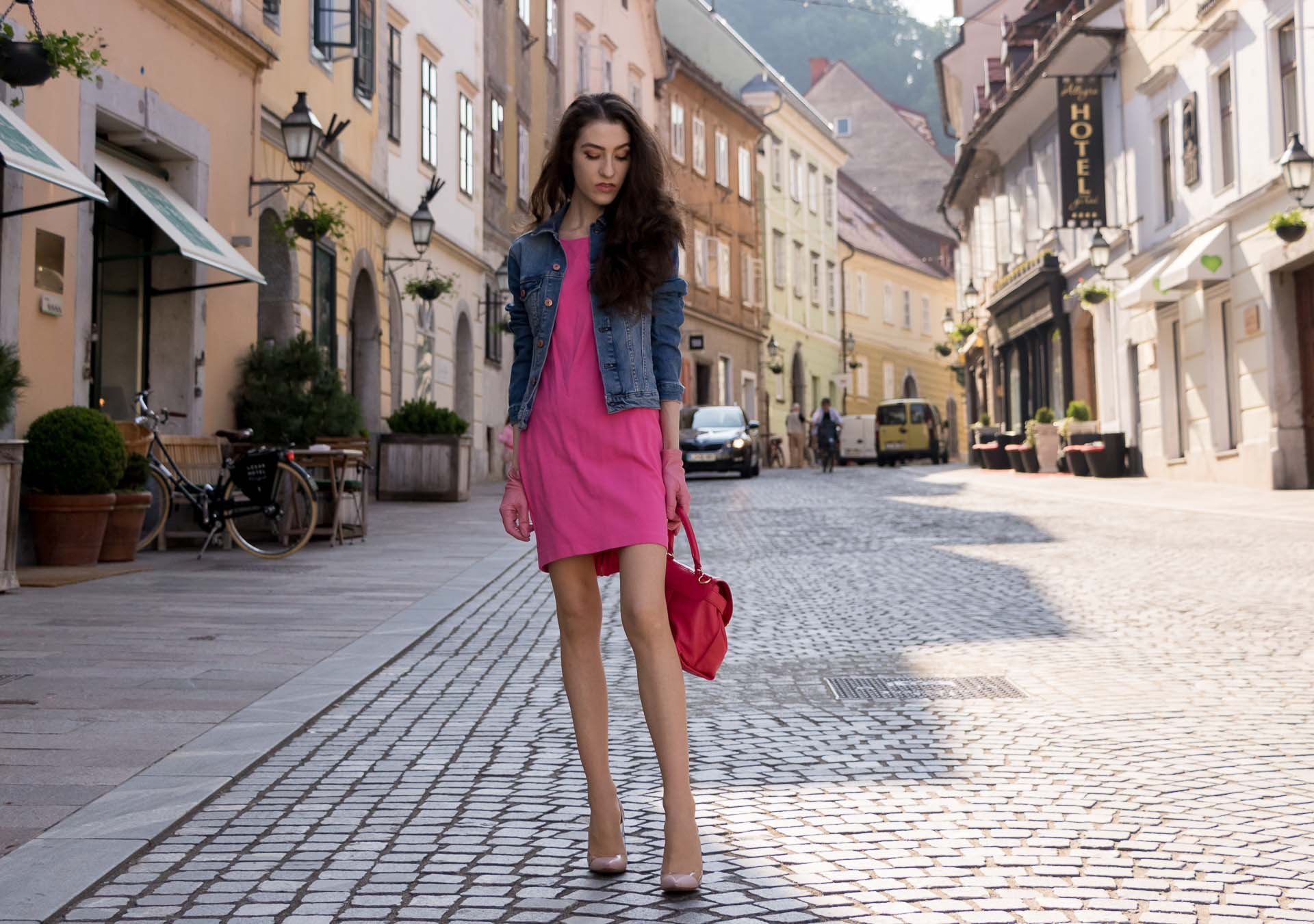 Veronika Lipar Fashion Blogger of Brunette from Wall Street dressed in H&M denim jacket, pink bodycon dress, blush Gianvito Rossi plexi pumps, pink Forzieri gloves, See by Chloé pink top handle bag, Adam Selman x Le Specs white cat eye Lolita sunglasses while standing on the street in Ljubljana