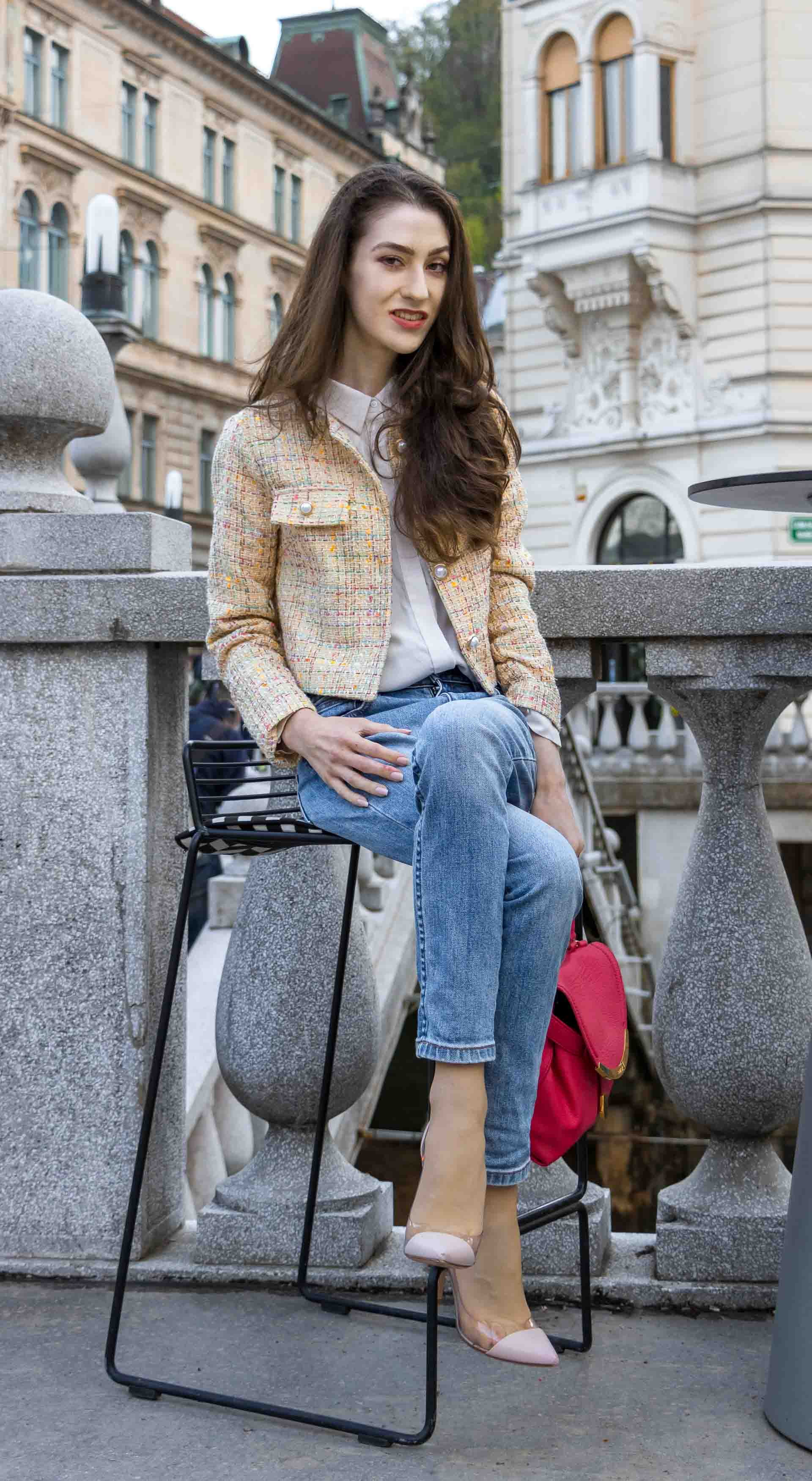 Veronika Lipar Fashion Blogger of Brunette from Wall Street wearing chic casual everyday spring outfit, the yellow tweed jacket from Storets, blue jeans from A.P.C., blush Gianvito Rossi plexi pumps, pink top handle bag and organza white sitting on a bar stole outdoors