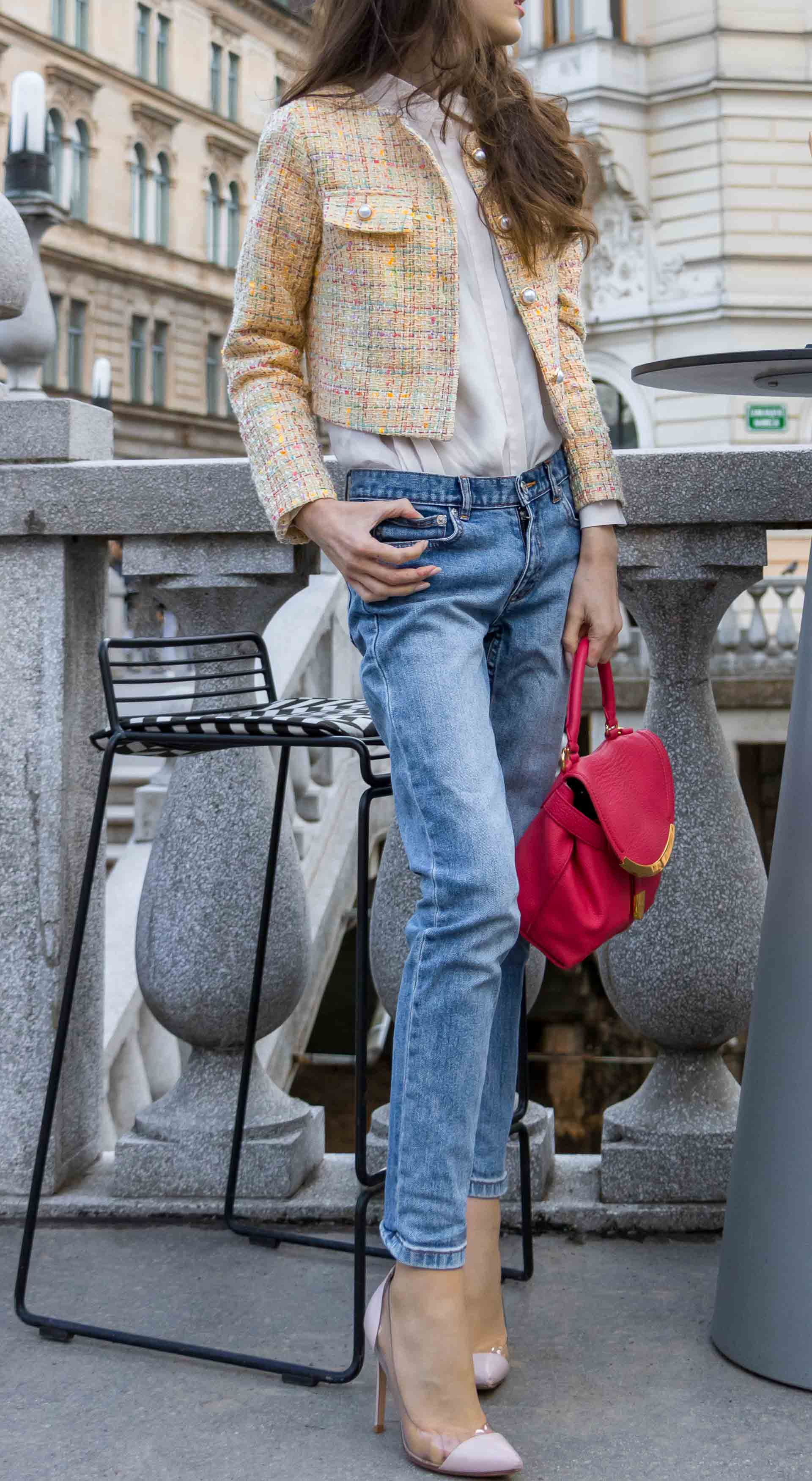 Veronika Lipar Fashion Blogger of Brunette from Wall Street wearing chic casual everyday spring outfit, the yellow tweed jacket from Storets, blue jeans from A.P.C., blush Gianvito Rossi plexi pumps, pink top handle bag and organza white shirt while standing by a bar stole outdoors