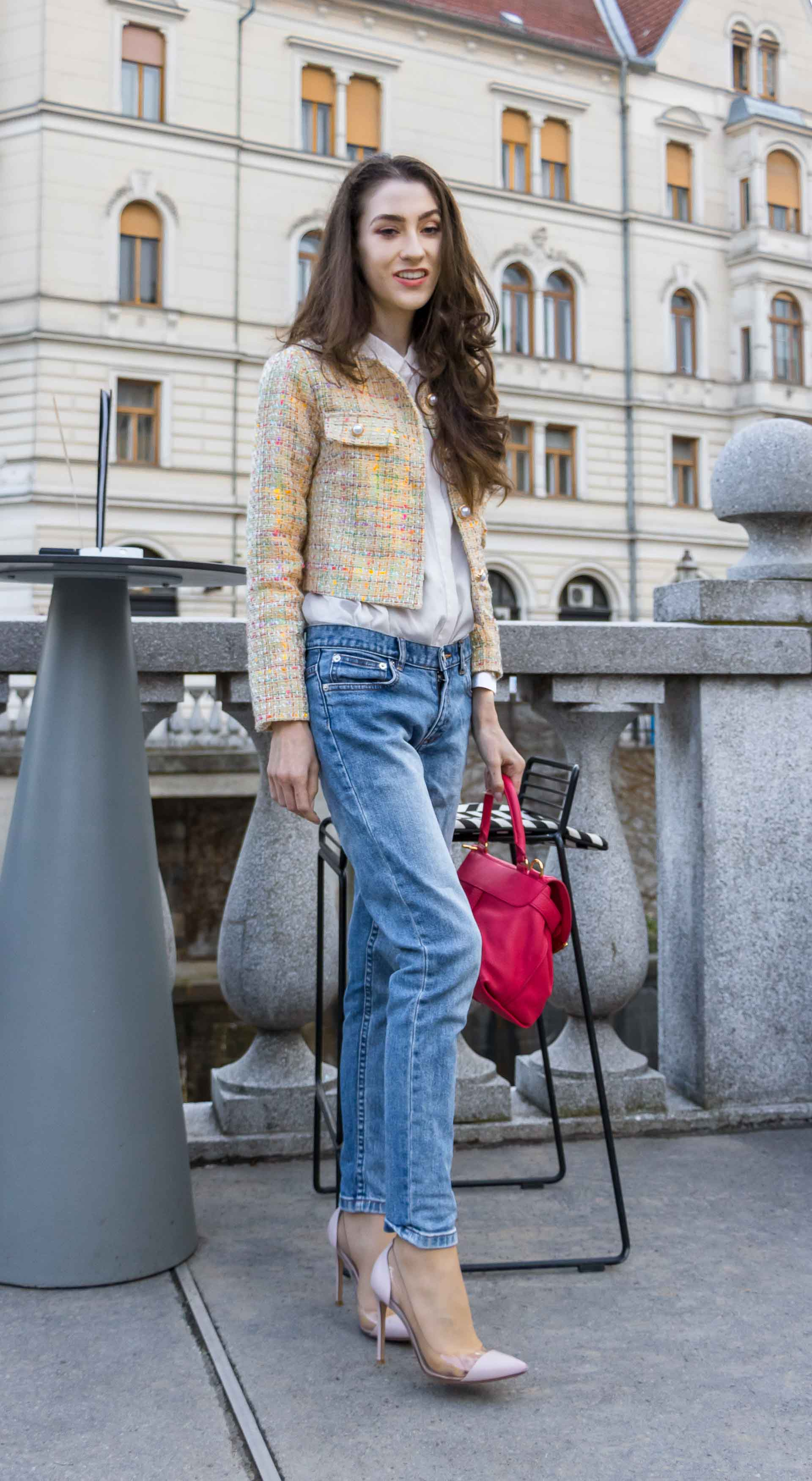 Veronika Lipar Fashion Blogger of Brunette from Wall Street dressed in chic casual everyday spring outfit, the yellow tweed jacket from Storets, blue jeans from A.P.C., blush Gianvito Rossi plexi pumps, pink top handle bag and organza white shirt while standing by a bar stole outdoors