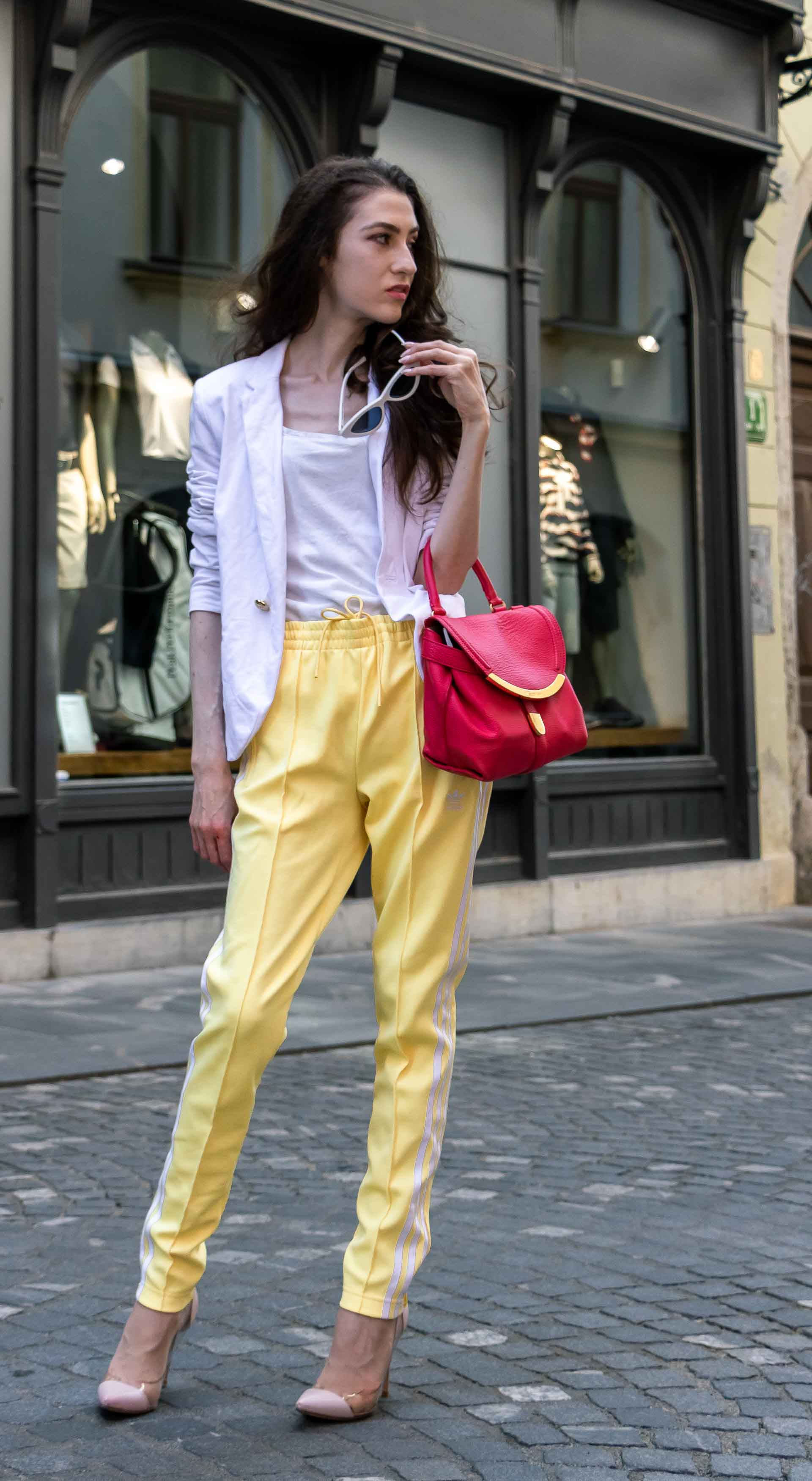 Veronika Lipar Fashion Blogger of Brunette from Wall Street dressed in chic casual white blazer, white H&M t-shirt, yellow Addidas track pants, See by Chloé pink top handle bag, Adam Selman x Le Specs white cat eye Lolita sunglasses, pink blush Gianvito Rossi plexi pumps on the street