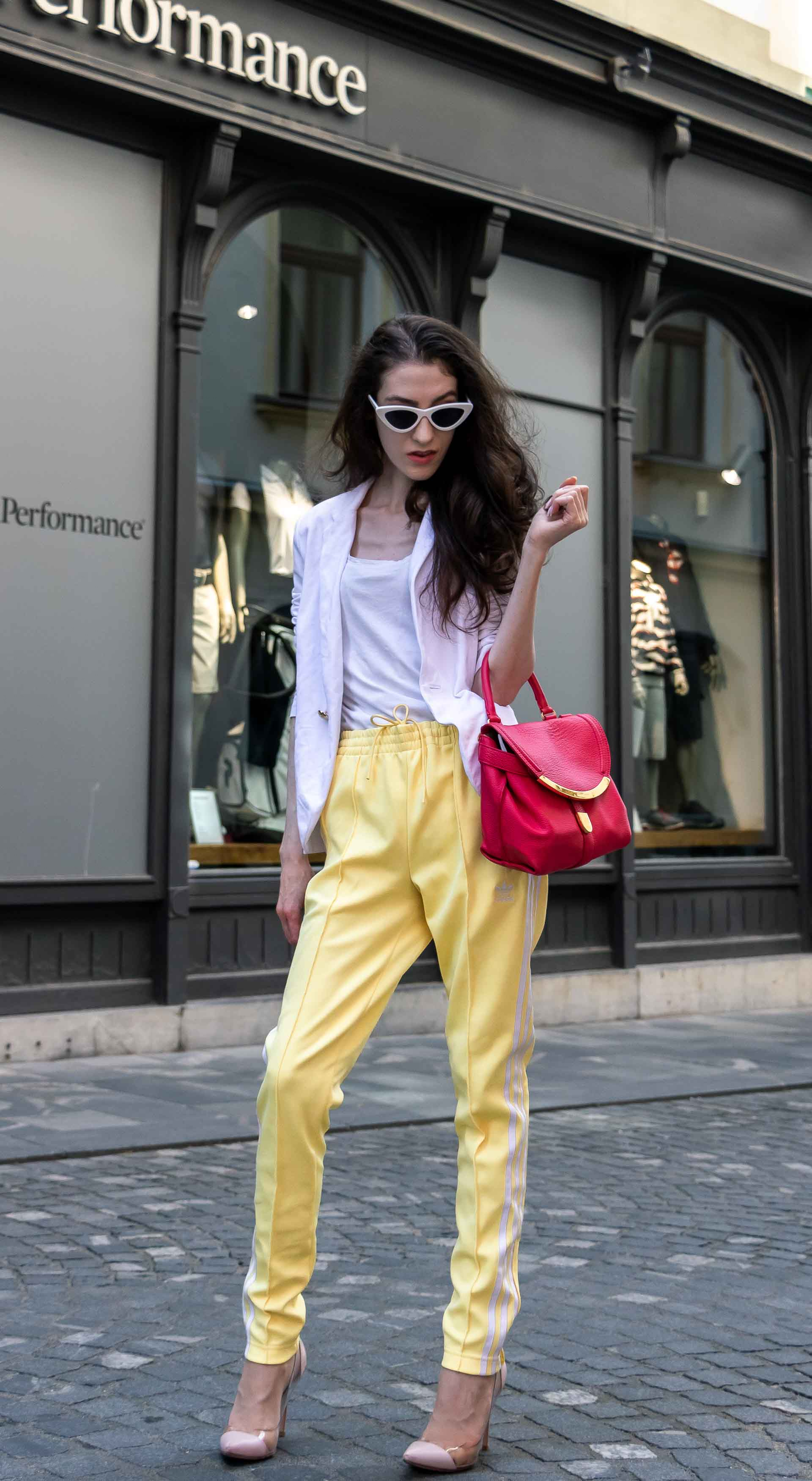 Veronika Lipar Fashion Editor of Brunette from Wall Street dressed in chic casual white blazer, white H&M t-shirt, yellow Addidas track pants, See by Chloé pink top handle bag, Adam Selman x Le Specs white cat eye Lolita sunglasses, pink blush Gianvito Rossi plexi pumps on the street