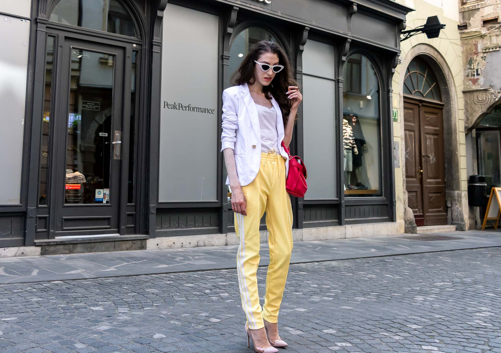 Veronika Lipar Fashion Editor of Brunette from Wall Street wearing white blazer, white H&M t-shirt, yellow Addidas track pants, See by Chloé pink top handle bag, Adam Selman x Le Specs white cat eye Lolita sunglasses, pink blush Gianvito Rossi plexi pumps in summer