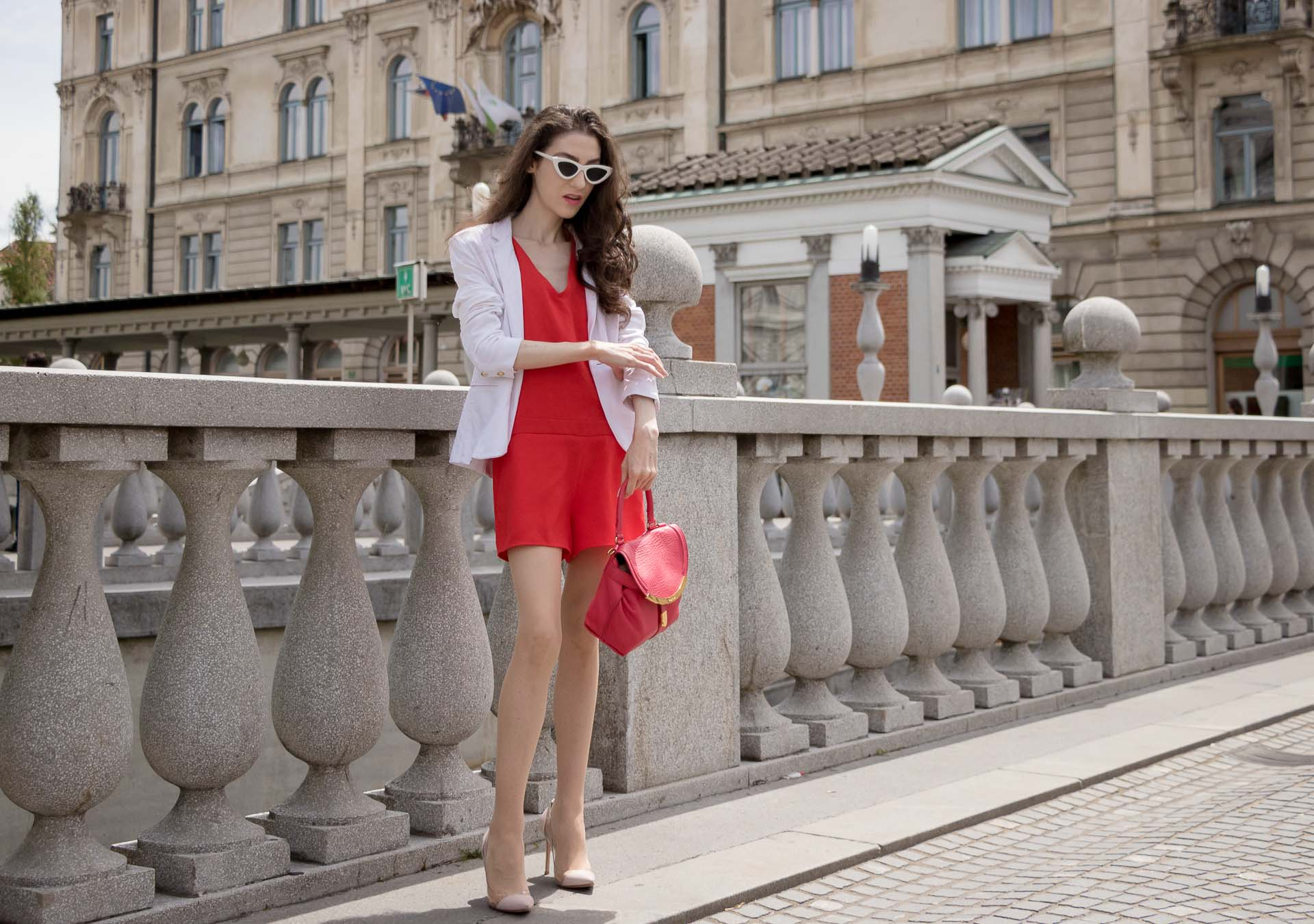 Veronika Lipar Fashion Blogger of Brunette from Wall Street wearing red playsuit, white blazer, Adam Selman x Le Specs white cat eye Lolita sunglasses, pink top handle See by Chloe bag, Gianvito Rossi plexi pumps
