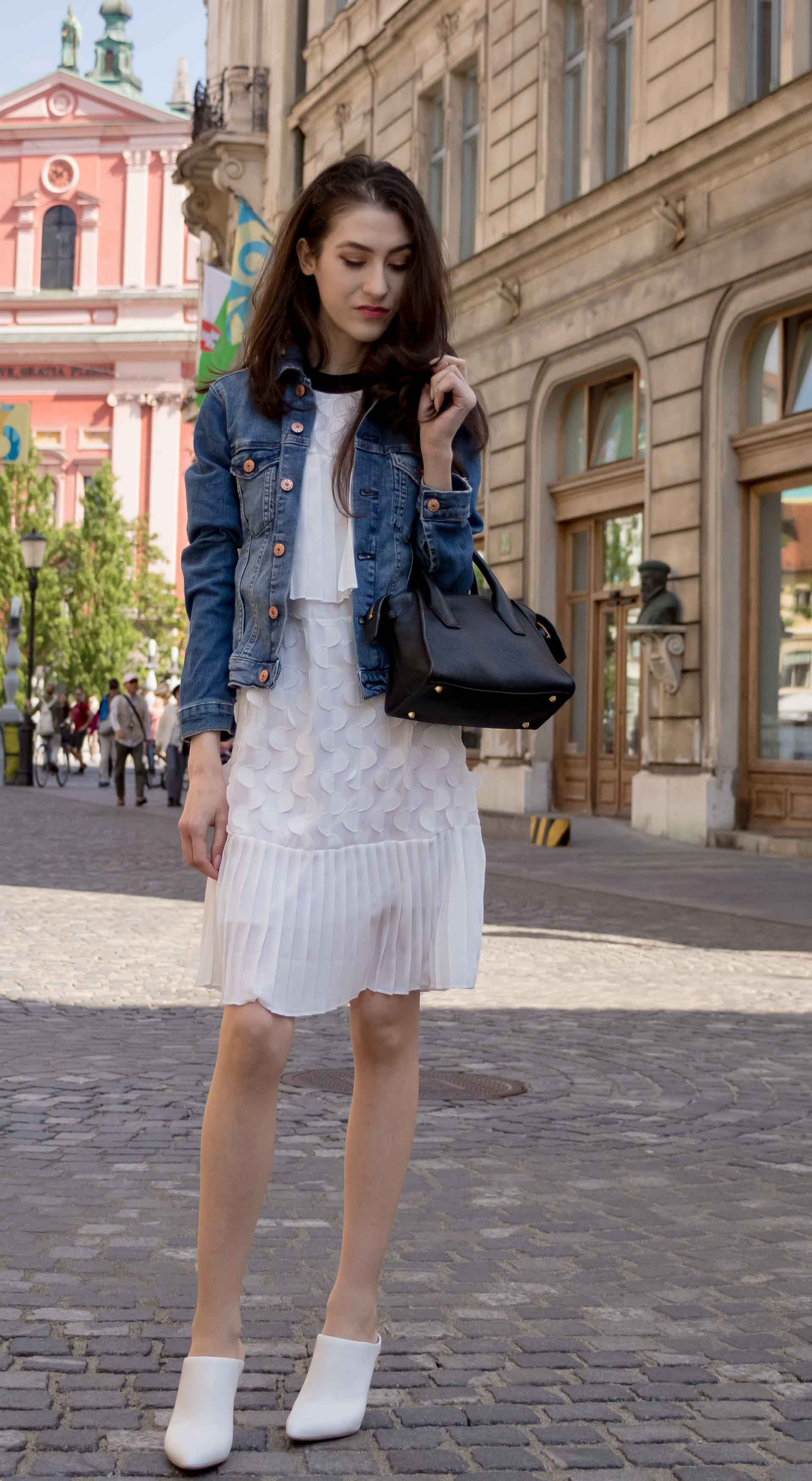 Veronika Lipar Fashion Editor of Brunette from Wall Street wearing H&M blue denim jacket, Storets white pleated short dress, white mules and Adam Selman x Le Specs white cat eye Lolita sunglasses, black small bag