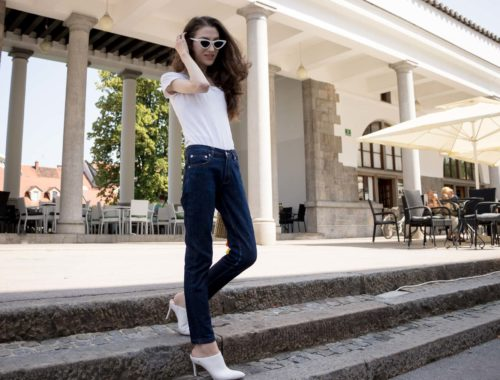 Veronika Lipar Fashion Editor of Brunette from Wall Street wearing summer basics dark blue tapered jeans from A.P.C., H&M white T-shirt, Nannacay basket bag, white mules and Adam Selman x Le Specs white cat eye Lolita sunglasses standing on the stairs