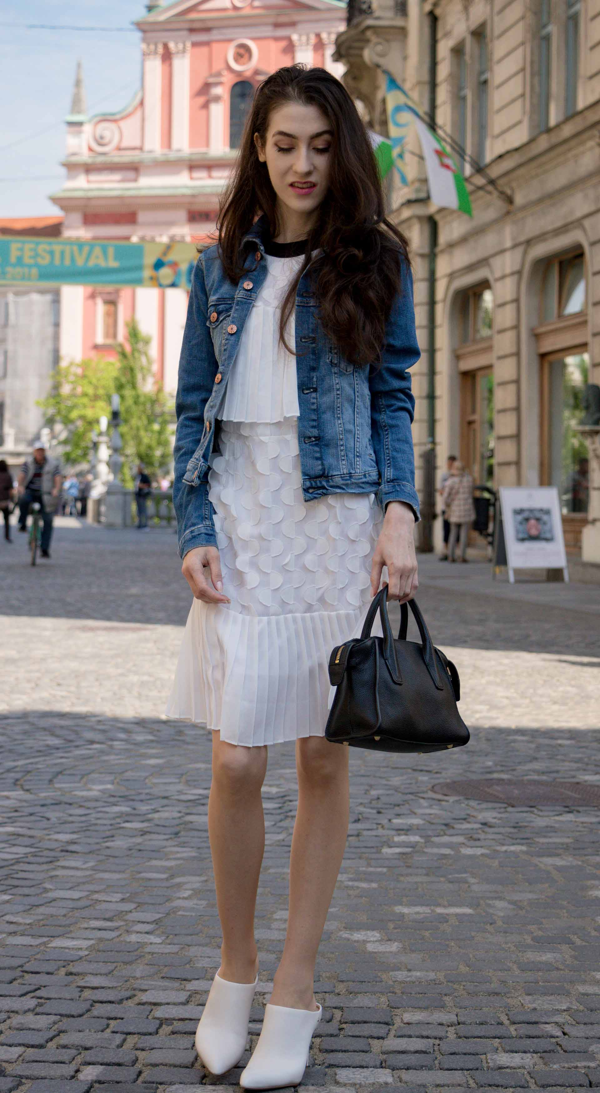 Veronika Lipar Fashion Editor of Brunette from Wall Street dressed in H&M blue denim jacket, Storets white pleated short dress, white mules and Adam Selman x Le Specs white cat eye Lolita sunglasses, black small bag standing on the street in Ljubljana