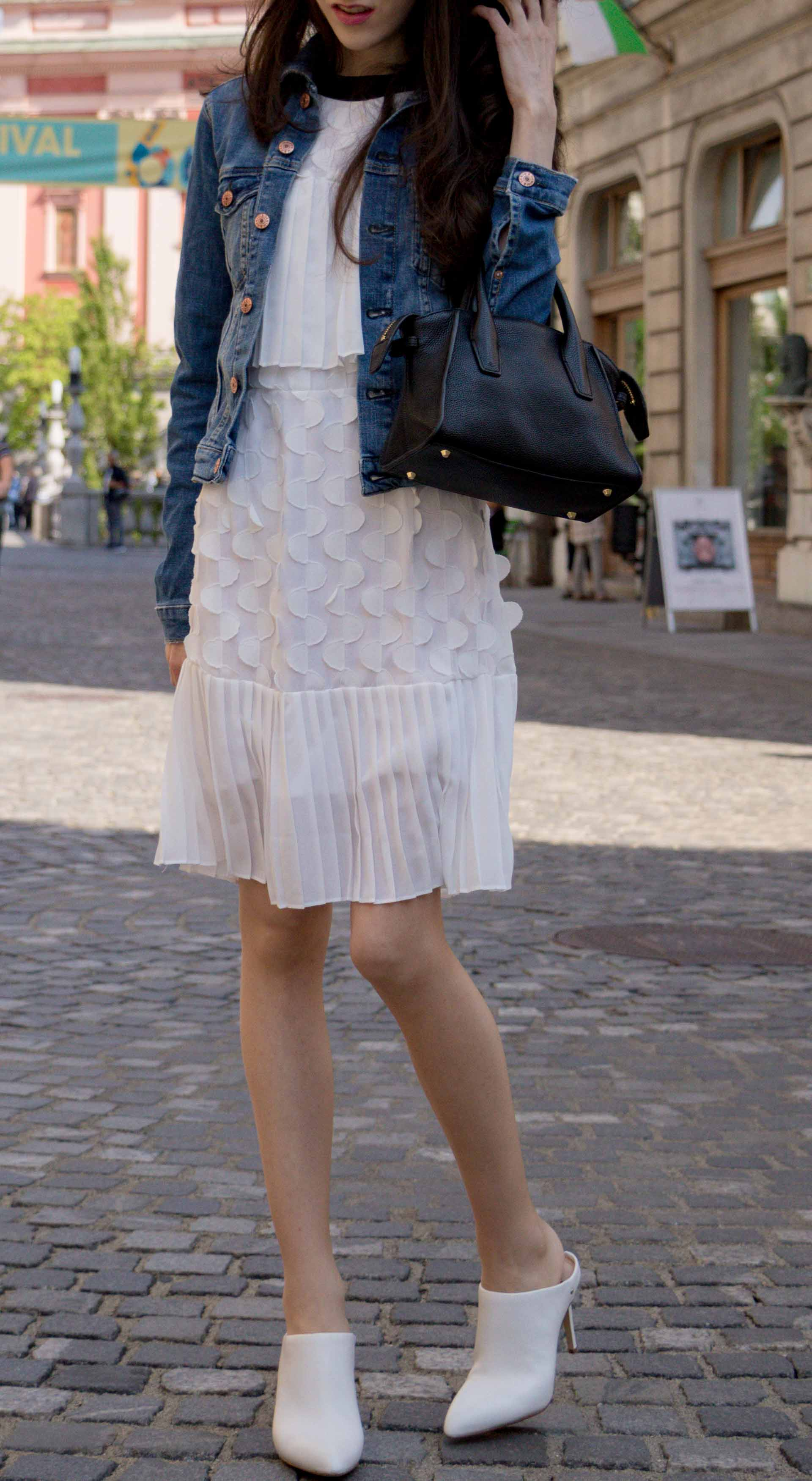 Veronika Lipar Fashion Editor of Brunette from Wall Street dressed in H&M blue denim jacket, Storets white pleated short dress, white mules and Adam Selman x Le Specs white cat eye Lolita sunglasses, black small bag dancing on the street