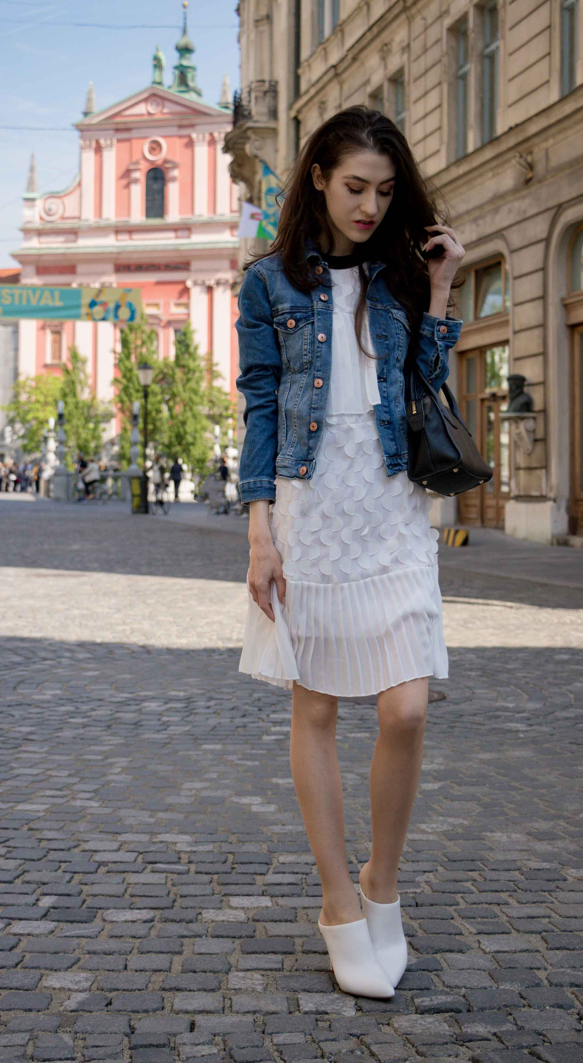 Veronika Lipar Fashion Editor of Brunette from Wall Street wearing H&M blue denim jacket, Storets white pleated short dress, white mules and Adam Selman x Le Specs white cat eye Lolita sunglasses, black small bag standing on the street