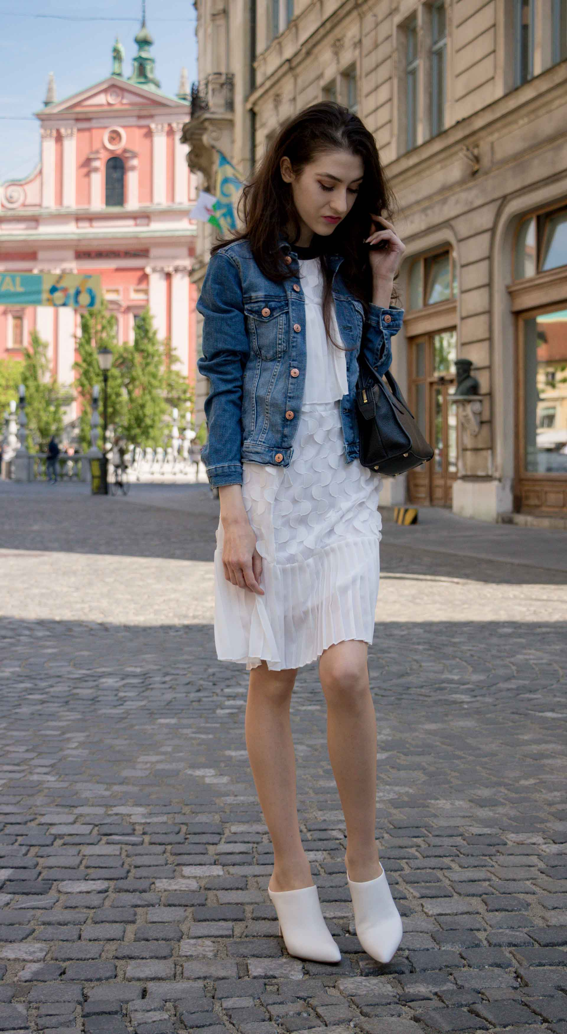 Veronika Lipar Fashion Editor of Brunette from Wall Street wearing H&M blue denim jacket, Storets white pleated short dress, white mules and Adam Selman x Le Specs white cat eye Lolita sunglasses, black small bag standing on the street in Ljubljana