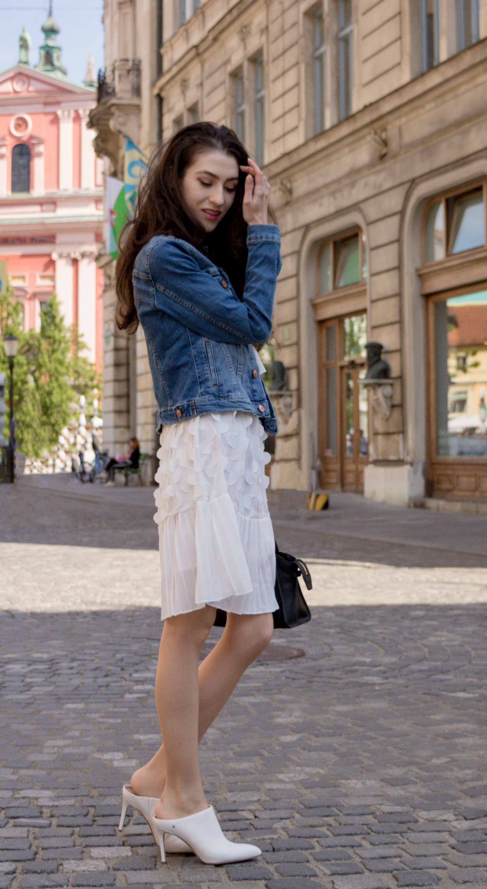 Veronika Lipar Fashion Editor of Brunette from Wall Street dressed in H&M blue denim jacket, Storets white pleated short dress, white mules and Adam Selman x Le Specs white cat eye Lolita sunglasses, black small bag standing on the street