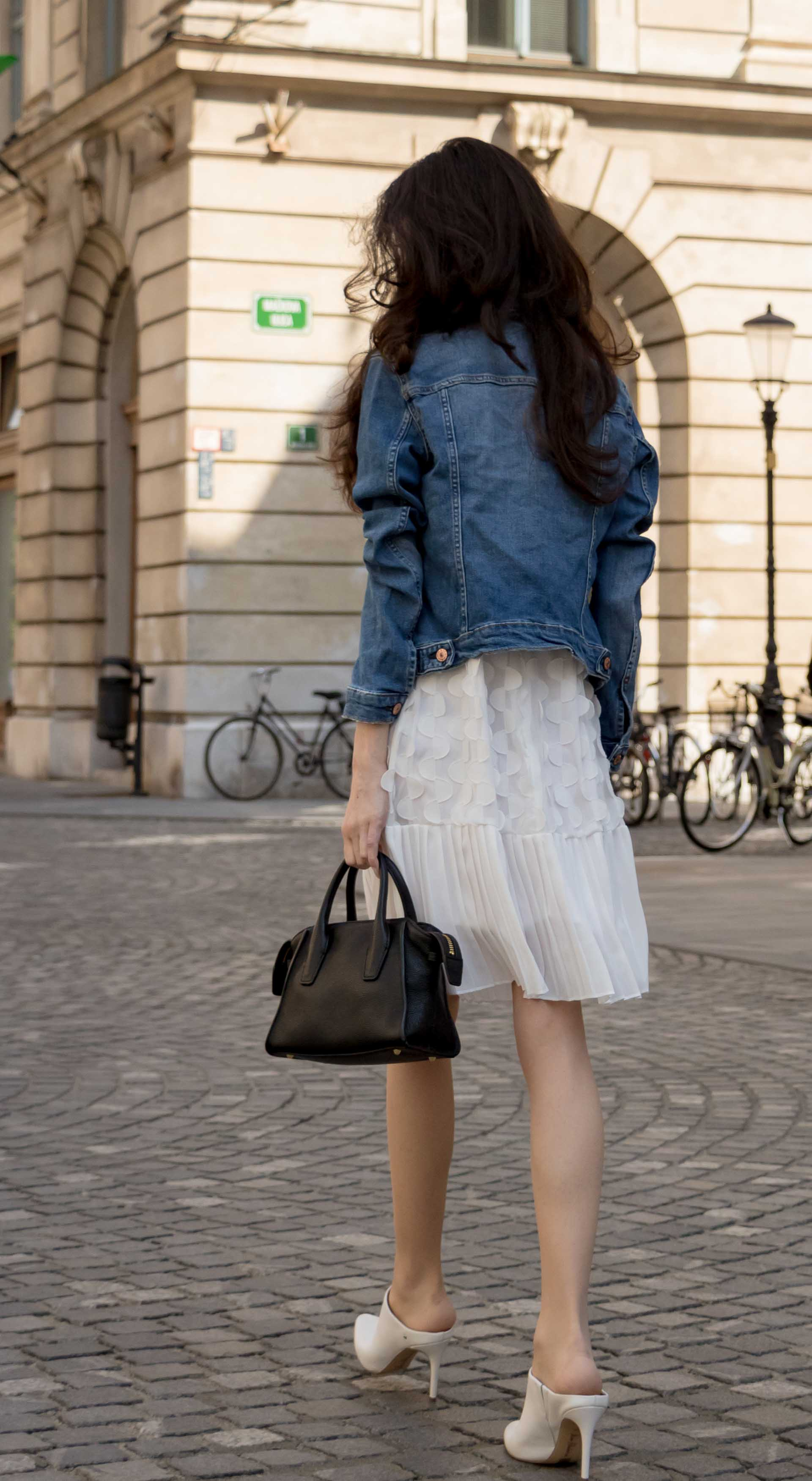 Veronika Lipar Fashion Editor of Brunette from Wall Street wearing H&M blue denim jacket, Storets white pleated short dress, white mules and Adam Selman x Le Specs white cat eye Lolita sunglasses, black small bag walking on the street