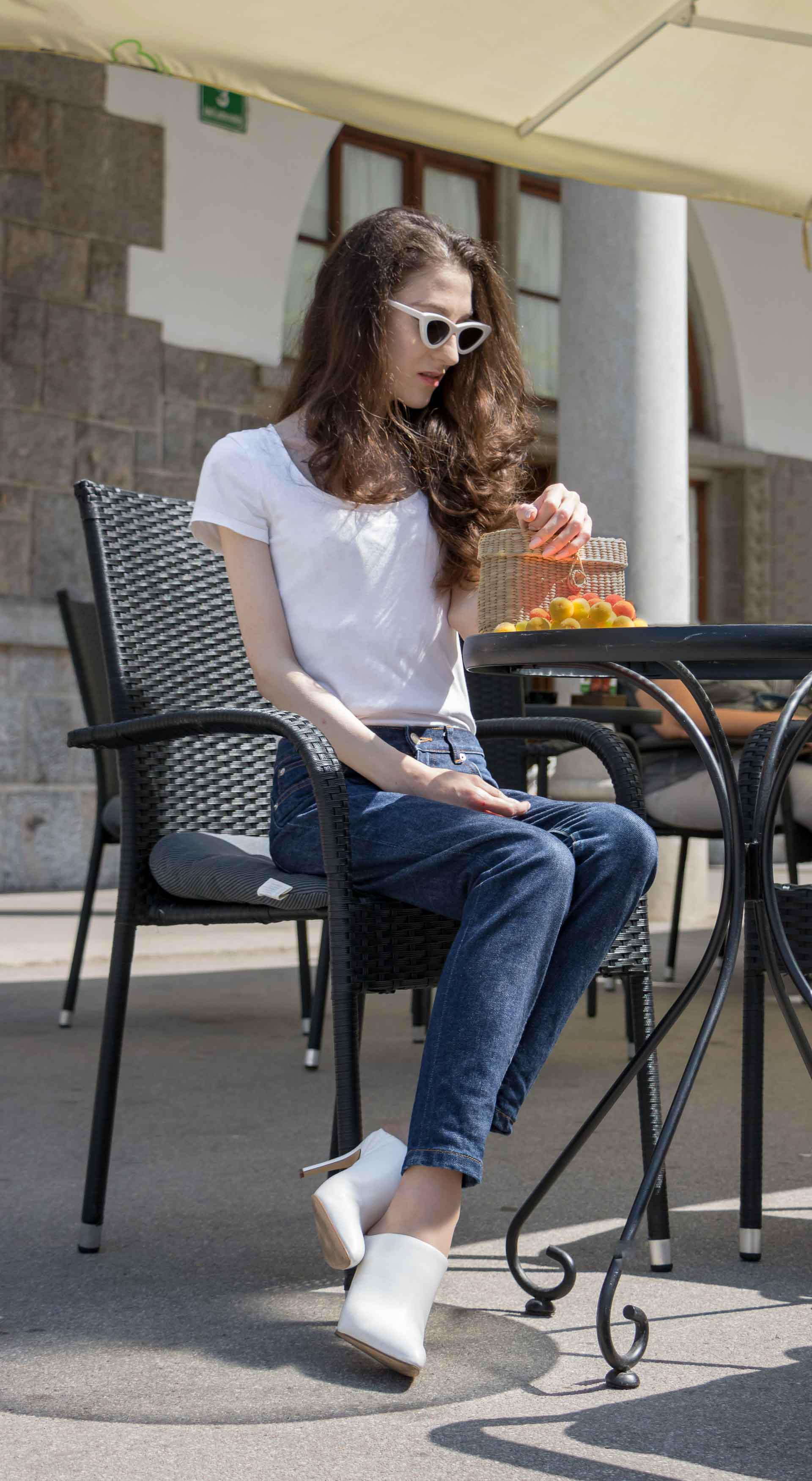 Veronika Lipar Fashion Editor of Brunette from Wall Street wearing basic summer outfit dark blue tapered jeans from A.P.C., H&M white T-shirt, Nannacay basket bag, white mules and Adam Selman x Le Specs white cat eye Lolita sunglasses sitting at the table