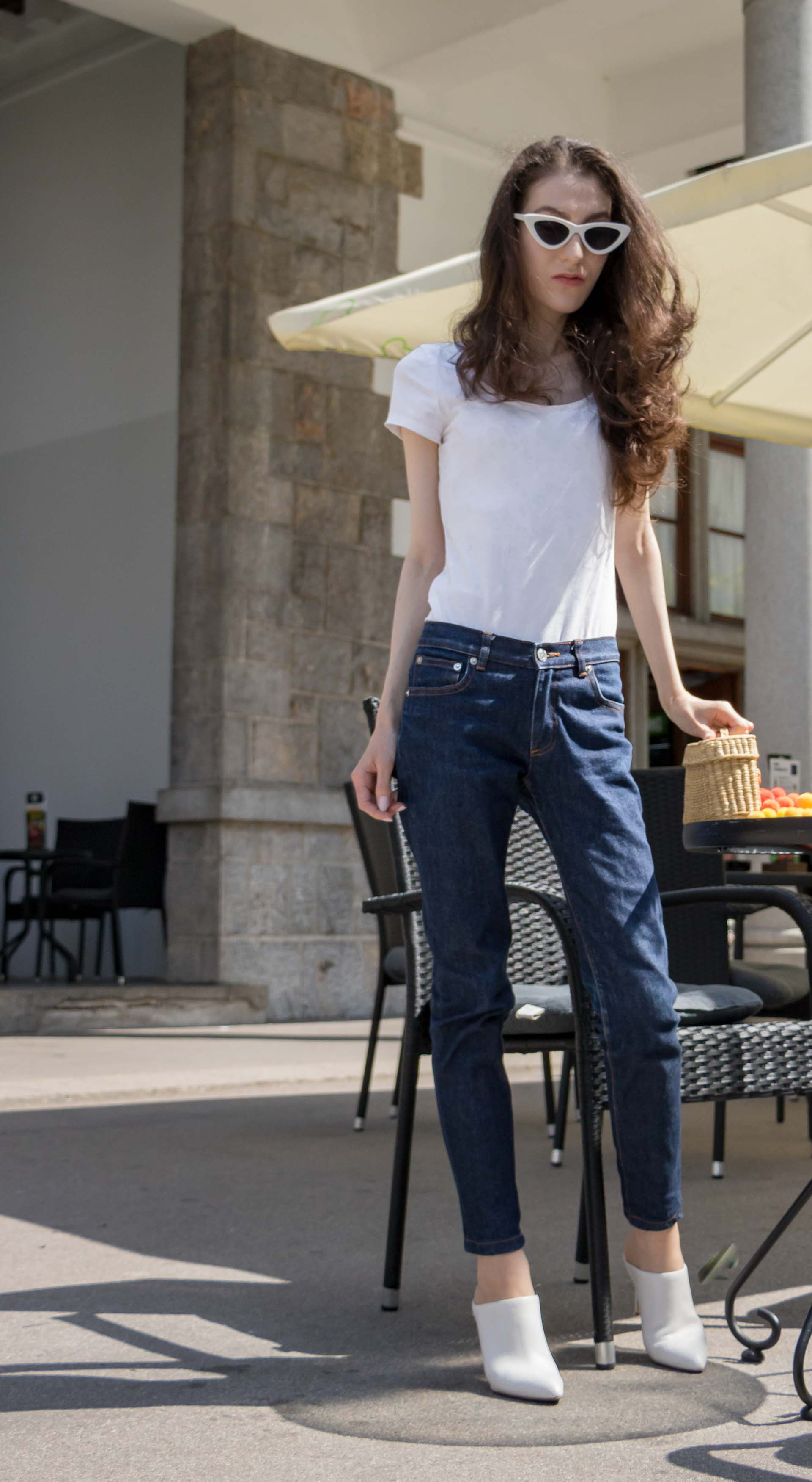Veronika Lipar Fashion Editor of Brunette from Wall Street wearing dark blue tapered jeans from A.P.C., H&M white T-shirt, Nannacay basket bag, white mules and Adam Selman x Le Specs white cat eye Lolita sunglasses on the street for drinks