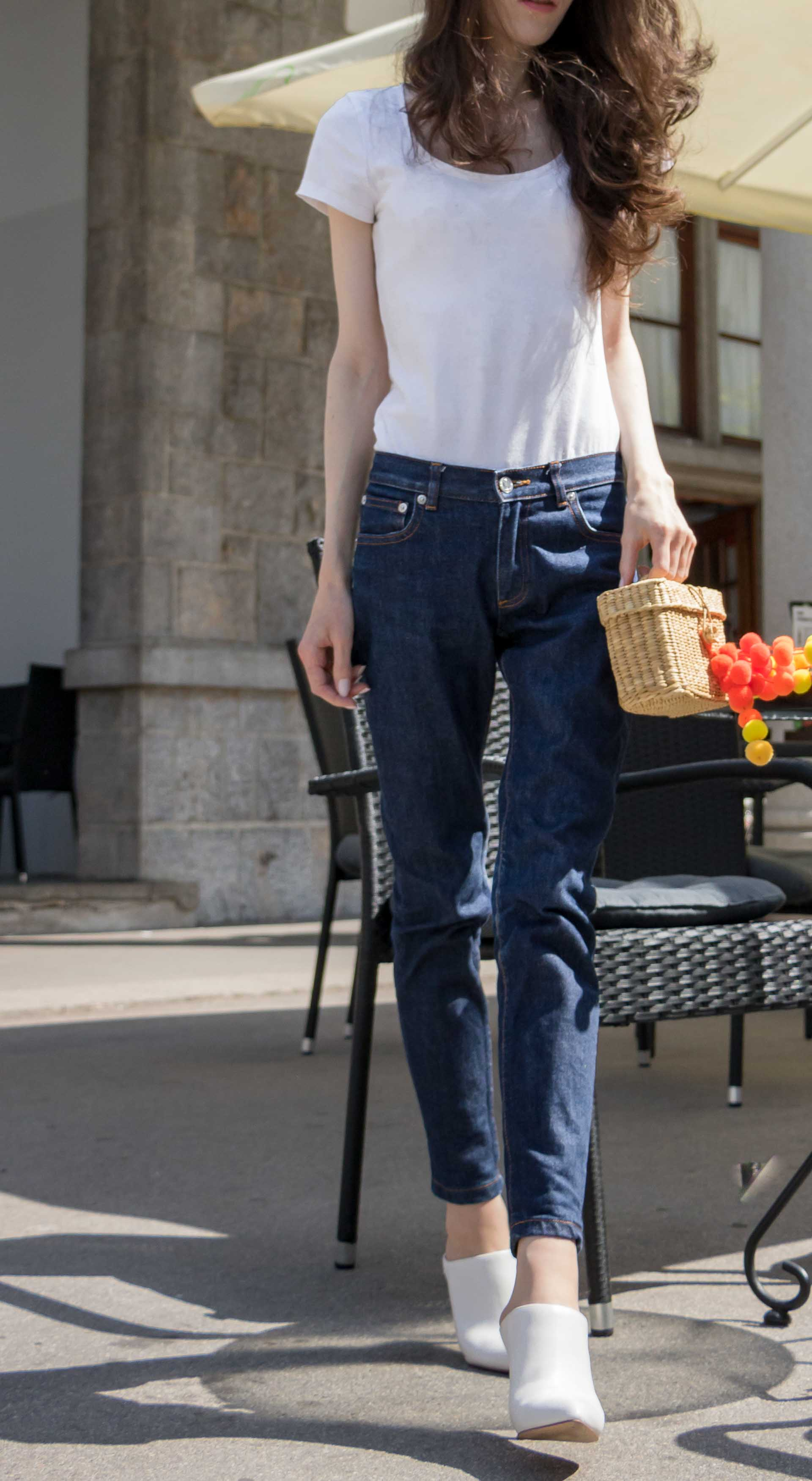 Veronika Lipar Fashion Editor of Brunette from Wall Street dressed in basic summer outfit dark blue tapered jeans from A.P.C., H&M white T-shirt, Nannacay basket bag, white mules and Adam Selman x Le Specs white cat eye Lolita sunglasses for drinks