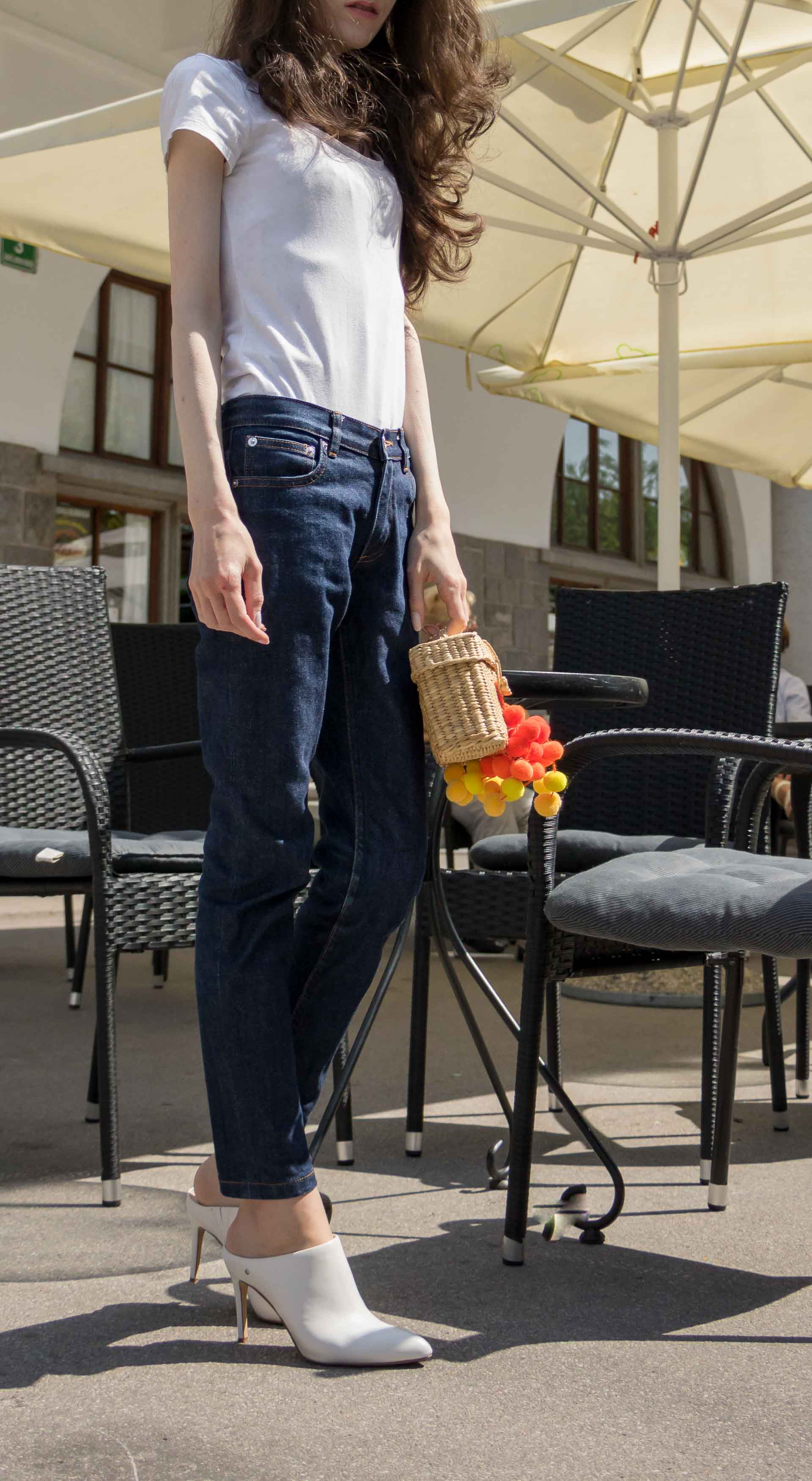Veronika Lipar Fashion Editor of Brunette from Wall Street dressed in dark blue tapered jeans from A.P.C., H&M white T-shirt, Nannacay basket bag, white mules and Adam Selman x Le Specs white cat eye Lolita sunglasses on the street for drinks