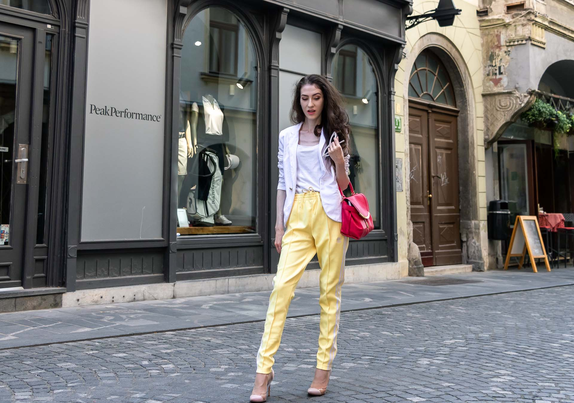 Veronika Lipar Fashion Editor of Brunette from Wall Street dressed in white blazer, white H&M t-shirt, yellow Addidas track pants, See by Chloé pink top handle bag, Adam Selman x Le Specs white cat eye Lolita sunglasses, pink blush Gianvito Rossi plexi pumps on the street in Ljubljana
