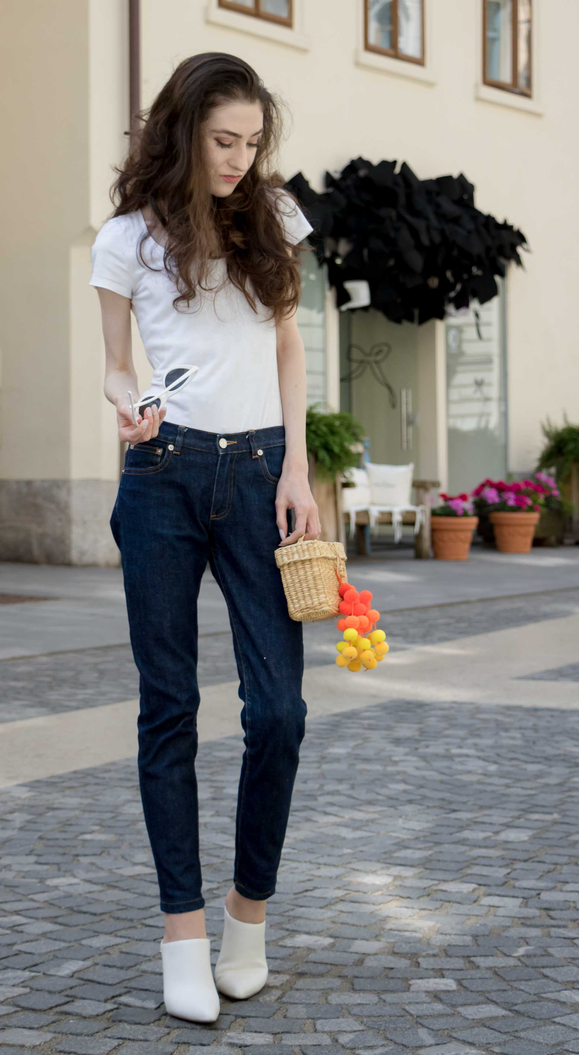 Veronika Lipar Fashion Editor of Brunette from Wall Street wearing dark blue tapered jeans from A.P.C., H&M white T-shirt, Nannacay basket bag, white mules and Adam Selman x Le Specs white cat eye Lolita sunglasses on the street