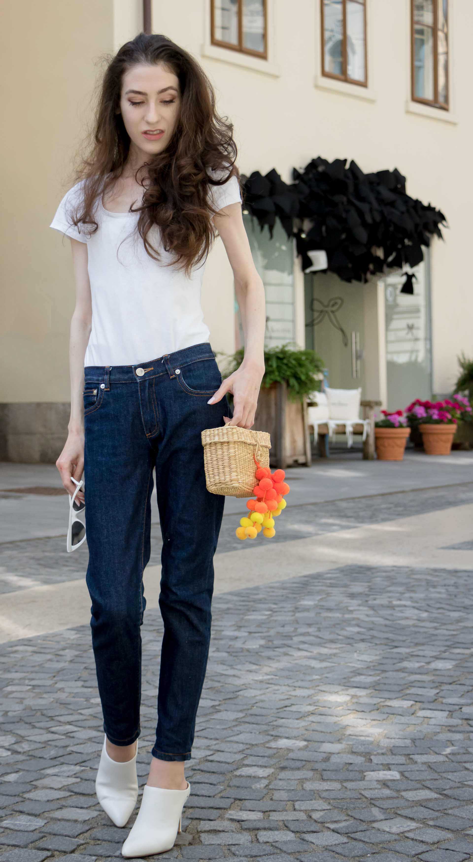 Veronika Lipar Fashion Editor of Brunette from Wall Street dressed in summer basics dark blue tapered jeans from A.P.C., H&M white T-shirt, Nannacay basket bag, white mules and Adam Selman x Le Specs white cat eye Lolita sunglasses on the street