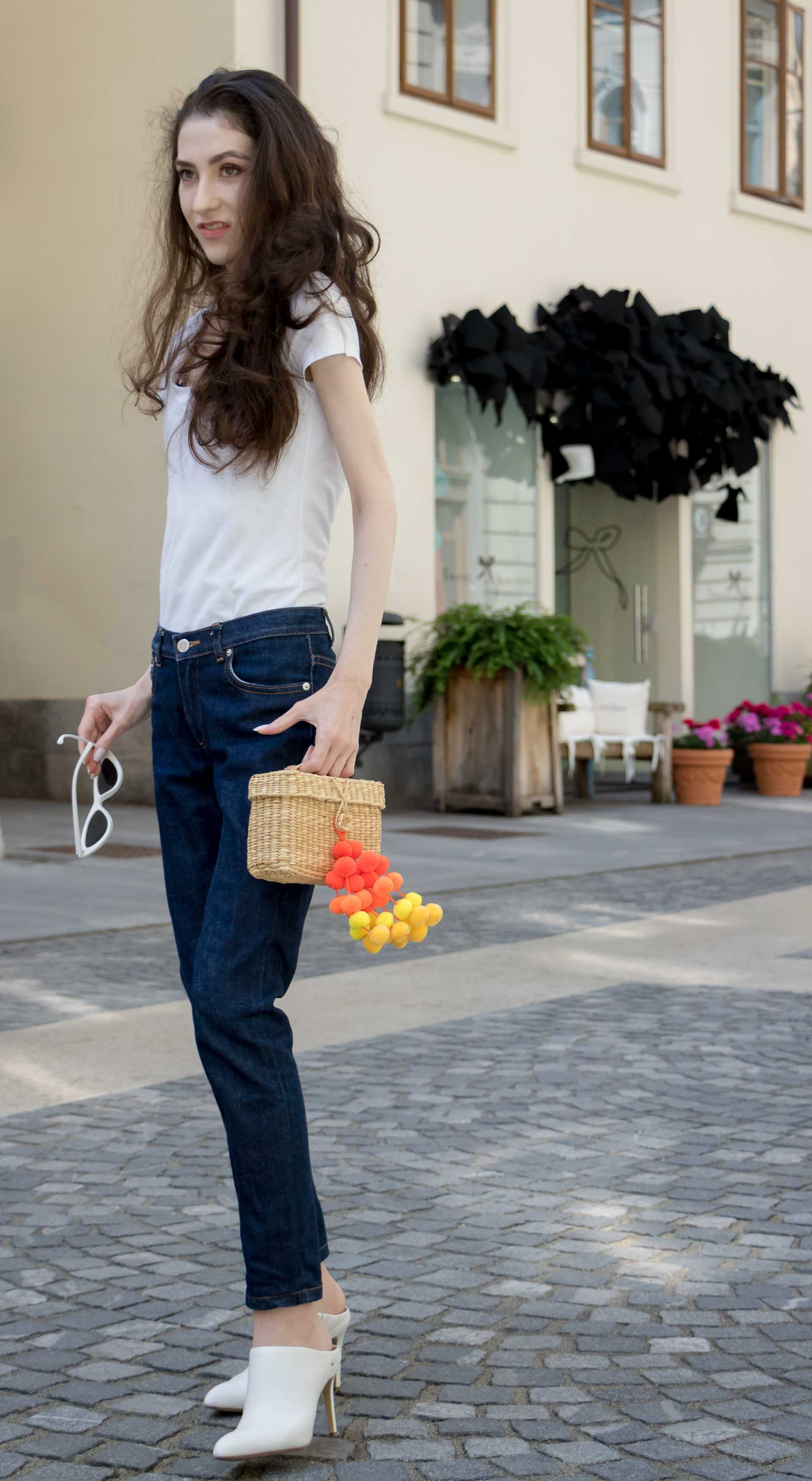 Veronika Lipar Fashion Editor of Brunette from Wall Street wearing basic summer outfit dark blue tapered jeans from A.P.C., H&M white T-shirt, Nannacay basket bag, white mules and Adam Selman x Le Specs white cat eye Lolita sunglasses on the street