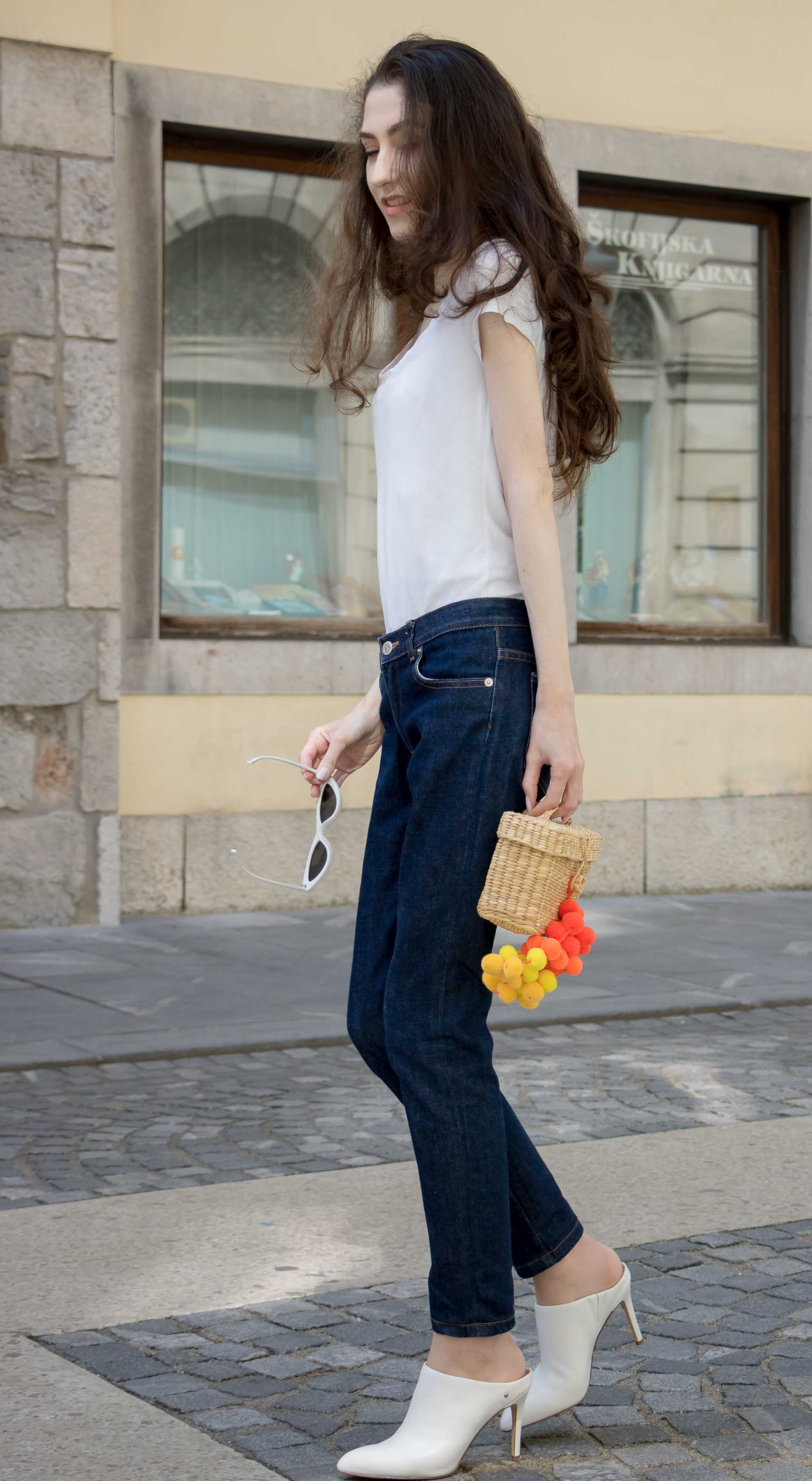 Veronika Lipar Fashion Editor of Brunette from Wall Street wearing summer basics dark blue tapered jeans from A.P.C., H&M white T-shirt, Nannacay basket bag, white mules and Adam Selman x Le Specs white cat eye Lolita sunglasses on the street