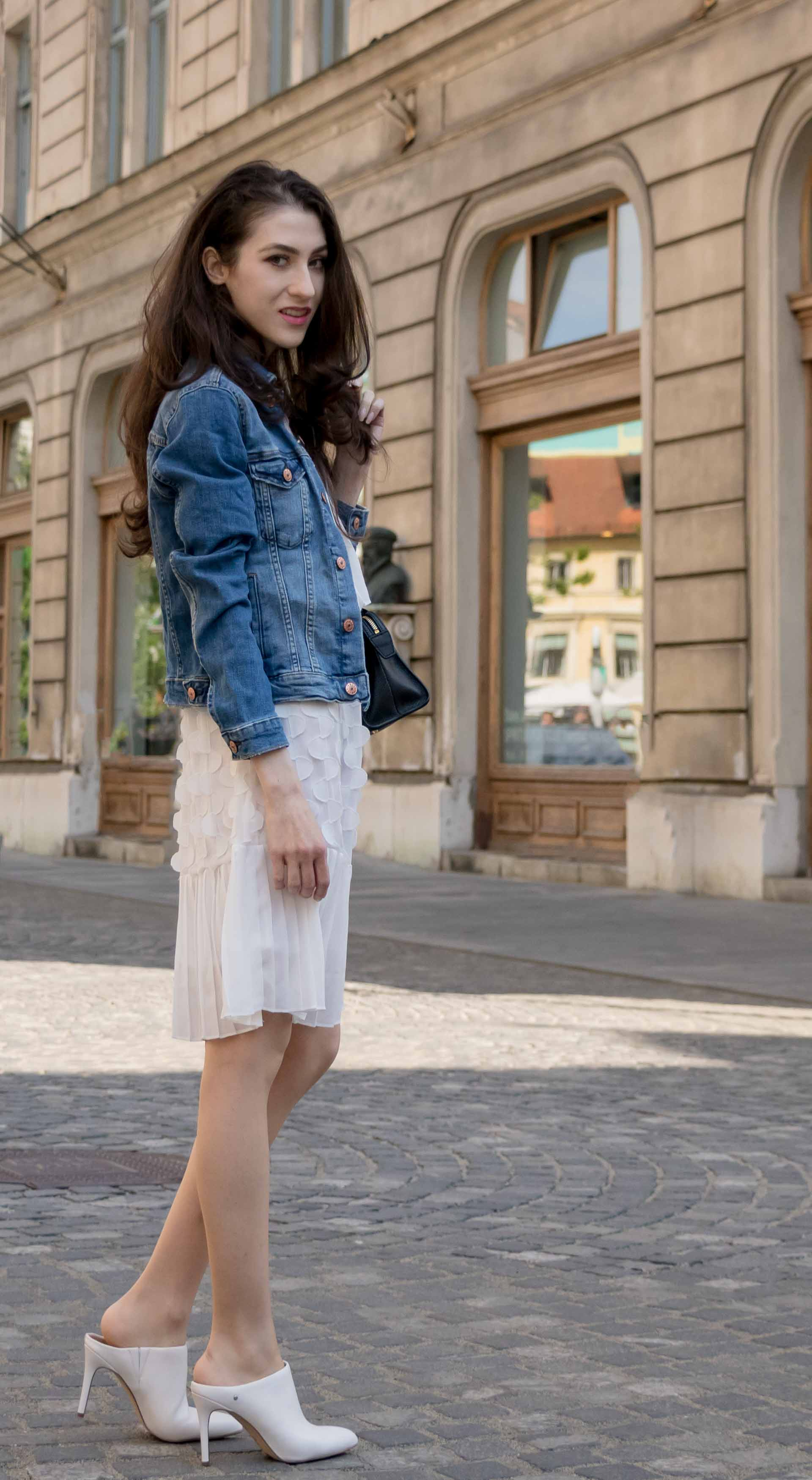 Veronika Lipar Fashion Editor of Brunette from Wall Street wearing H&M blue denim jacket, Storets white pleated short dress, white mules and Adam Selman x Le Specs white cat eye Lolita sunglasses, black small bag in Ljubljana