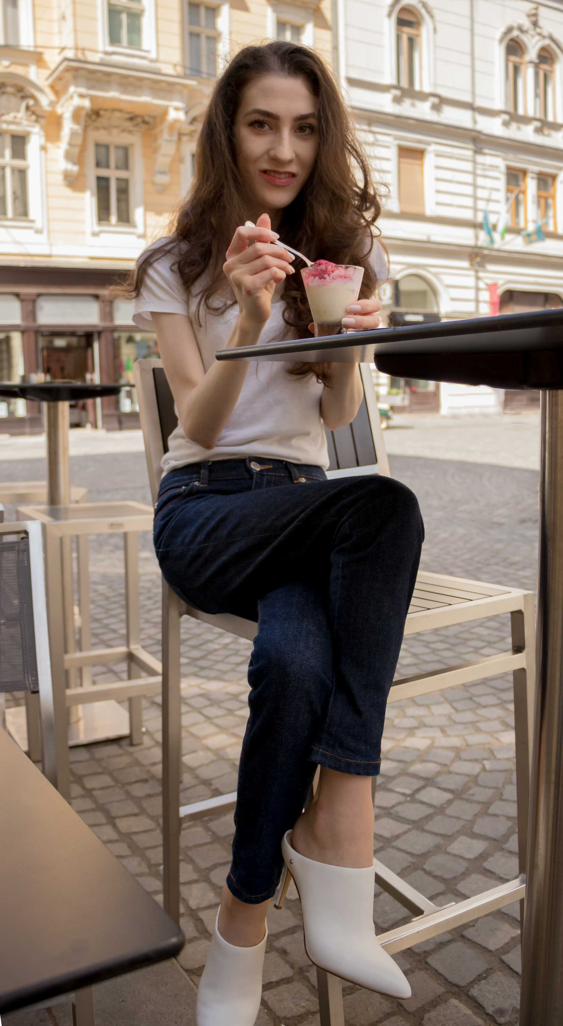 Veronika Lipar Fashion Editor of Brunette from Wall Street dressed in basic summer outfit dark blue tapered jeans from A.P.C., H&M white T-shirt, Nannacay basket bag, white mules and Adam Selman x Le Specs white cat eye Lolita sunglasses eating ice cream