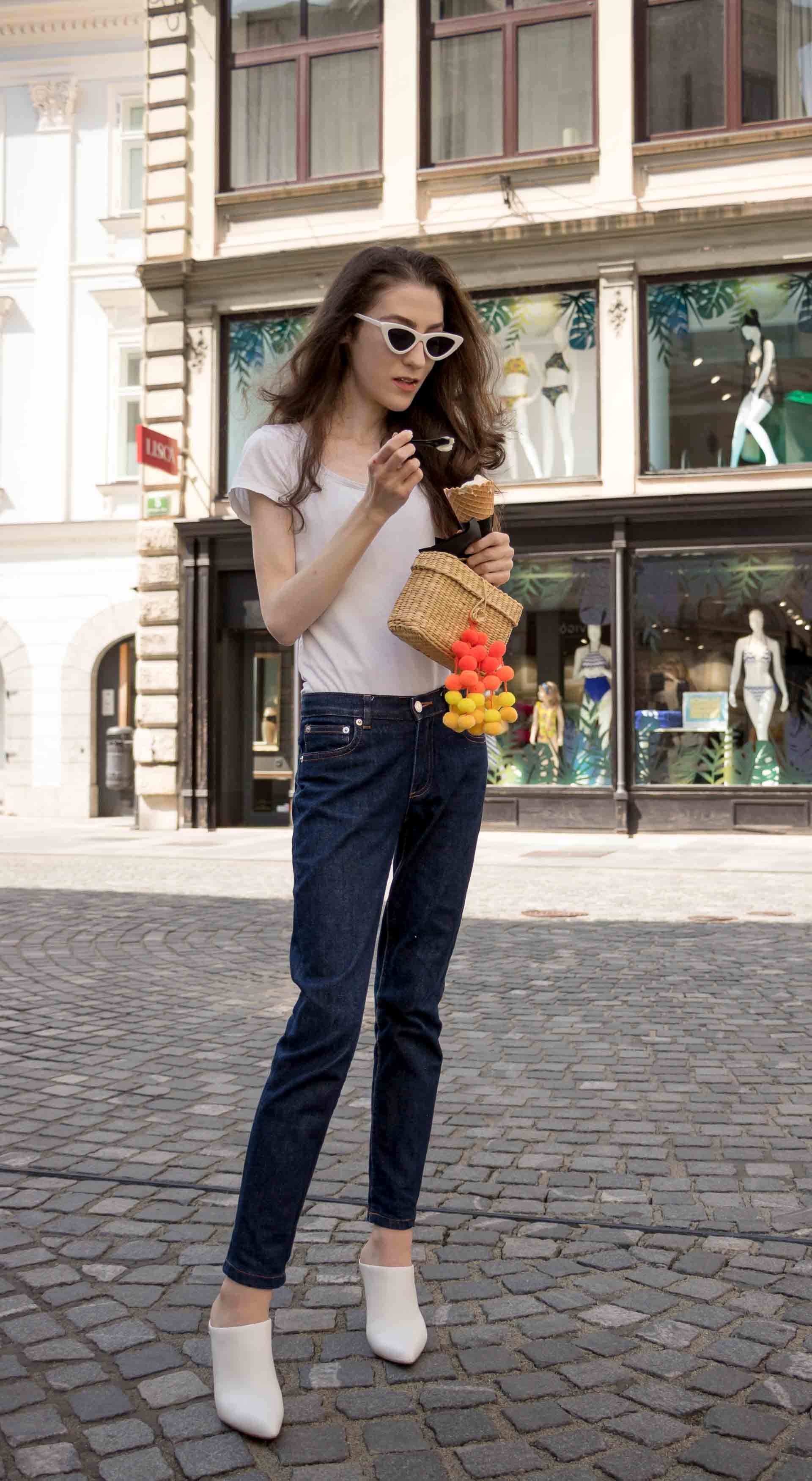 Veronika Lipar Fashion Editor of Brunette from Wall Street dressed in dark blue tapered jeans from A.P.C., H&M white T-shirt, Nannacay basket bag, white mules and Adam Selman x Le Specs white cat eye Lolita sunglasses on the street eating ice cream