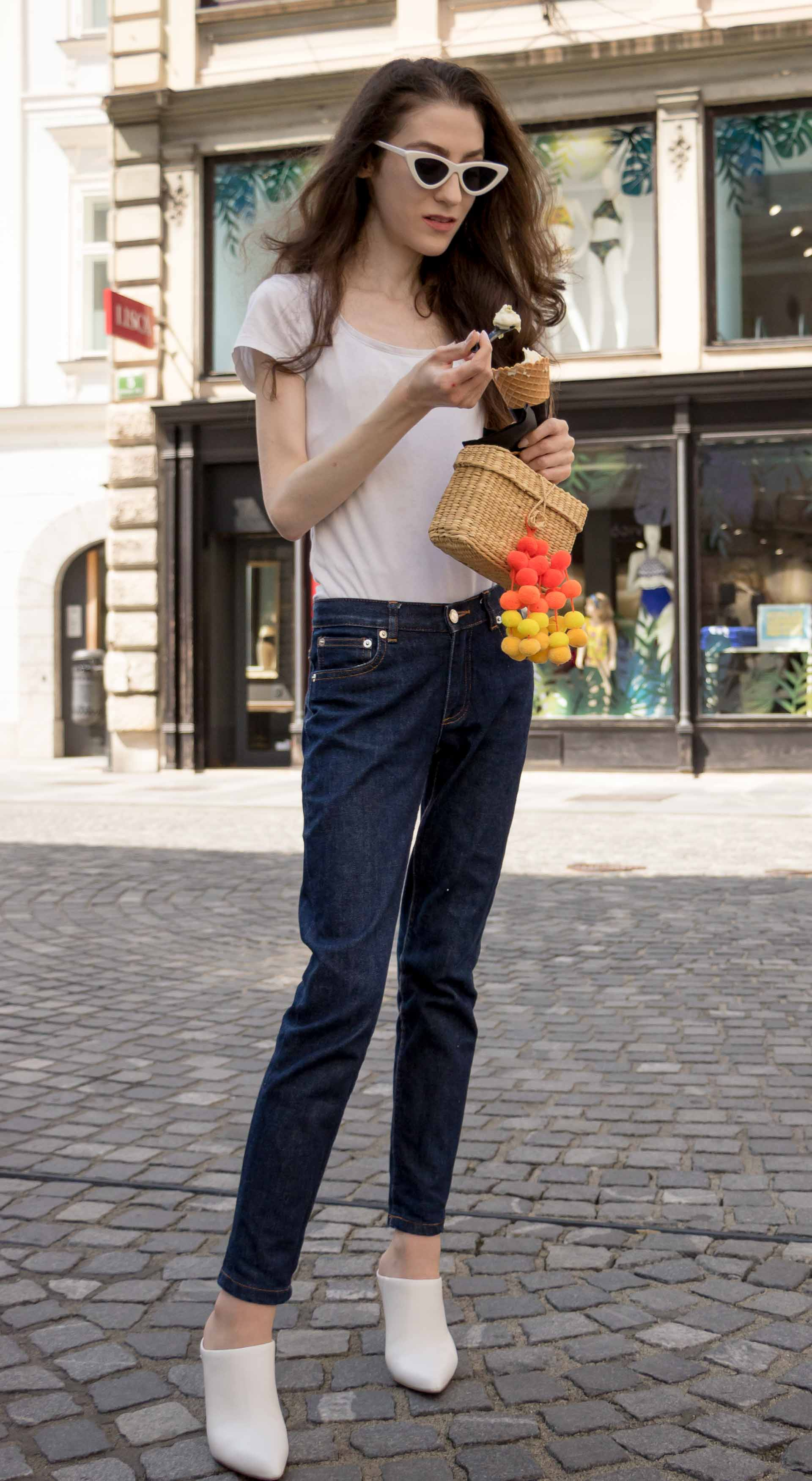 Veronika Lipar Fashion Editor of Brunette from Wall Street wearing summer basics dark blue tapered jeans from A.P.C., H&M white T-shirt, Nannacay basket bag, white mules and Adam Selman x Le Specs white cat eye Lolita sunglasses eating ice cream