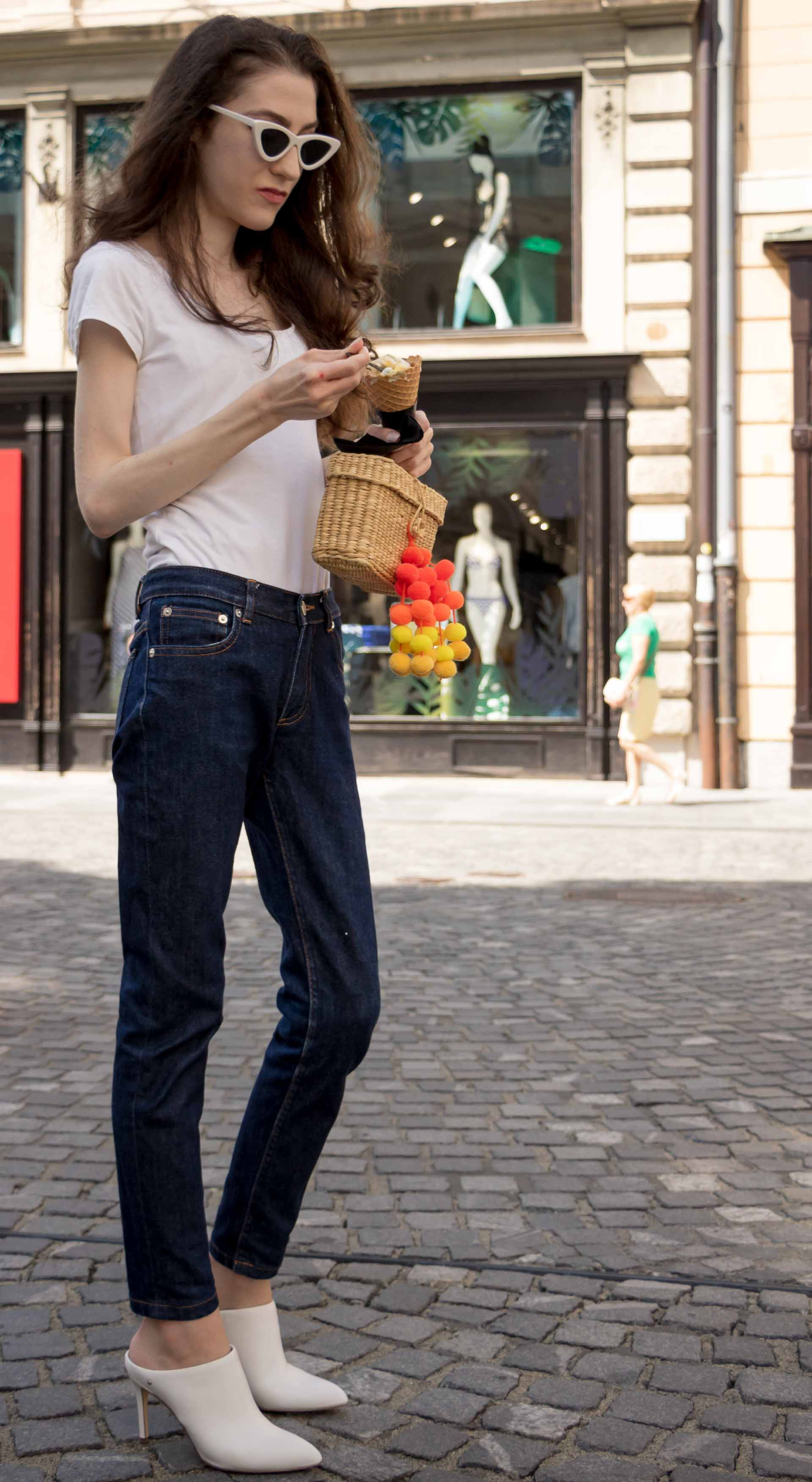 Veronika Lipar Fashion Editor of Brunette from Wall Street wearing dark blue tapered jeans from A.P.C., H&M white T-shirt, Nannacay basket bag, white mules and Adam Selman x Le Specs white cat eye Lolita sunglasses on the street eating ice cream
