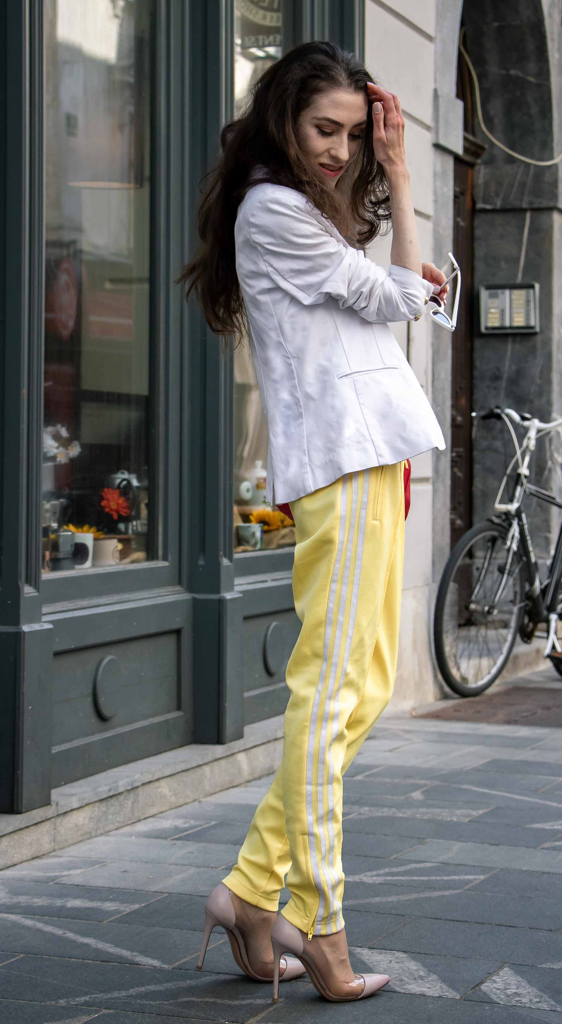 Veronika Lipar Fashion Blogger of Brunette from Wall Street dressed in white blazer, white H&M t-shirt, yellow Addidas track pants, See by Chloé pink top handle bag, Adam Selman x Le Specs white cat eye Lolita sunglasses, pink blush Gianvito Rossi plexi pumps in summer