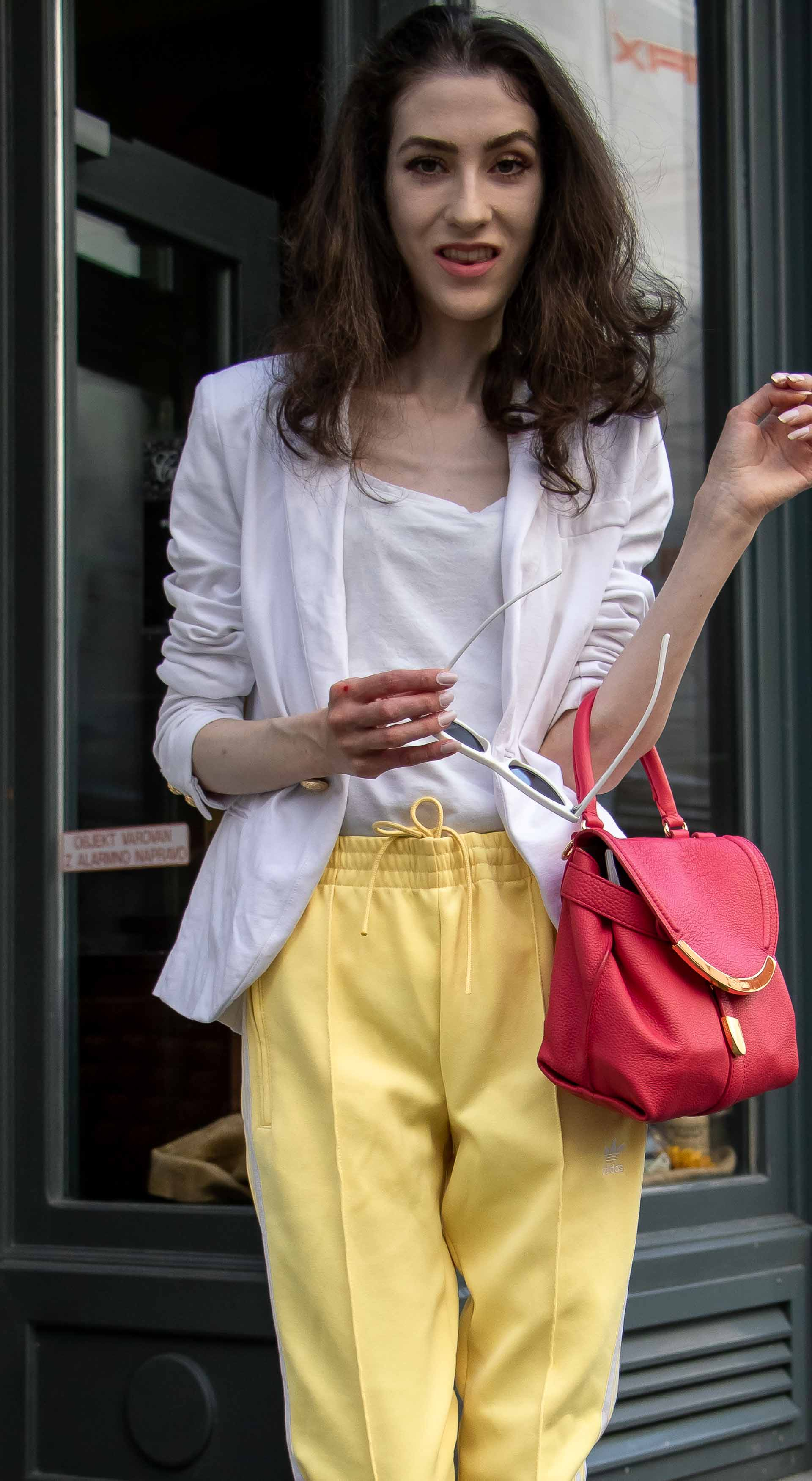 Veronika Lipar Fashion Blogger of Brunette from Wall Street wearing white blazer, white H&M t-shirt, yellow Addidas track pants, See by Chloé pink top handle bag, Adam Selman x Le Specs white cat eye Lolita sunglasses, pink blush Gianvito Rossi plexi pumps in summer