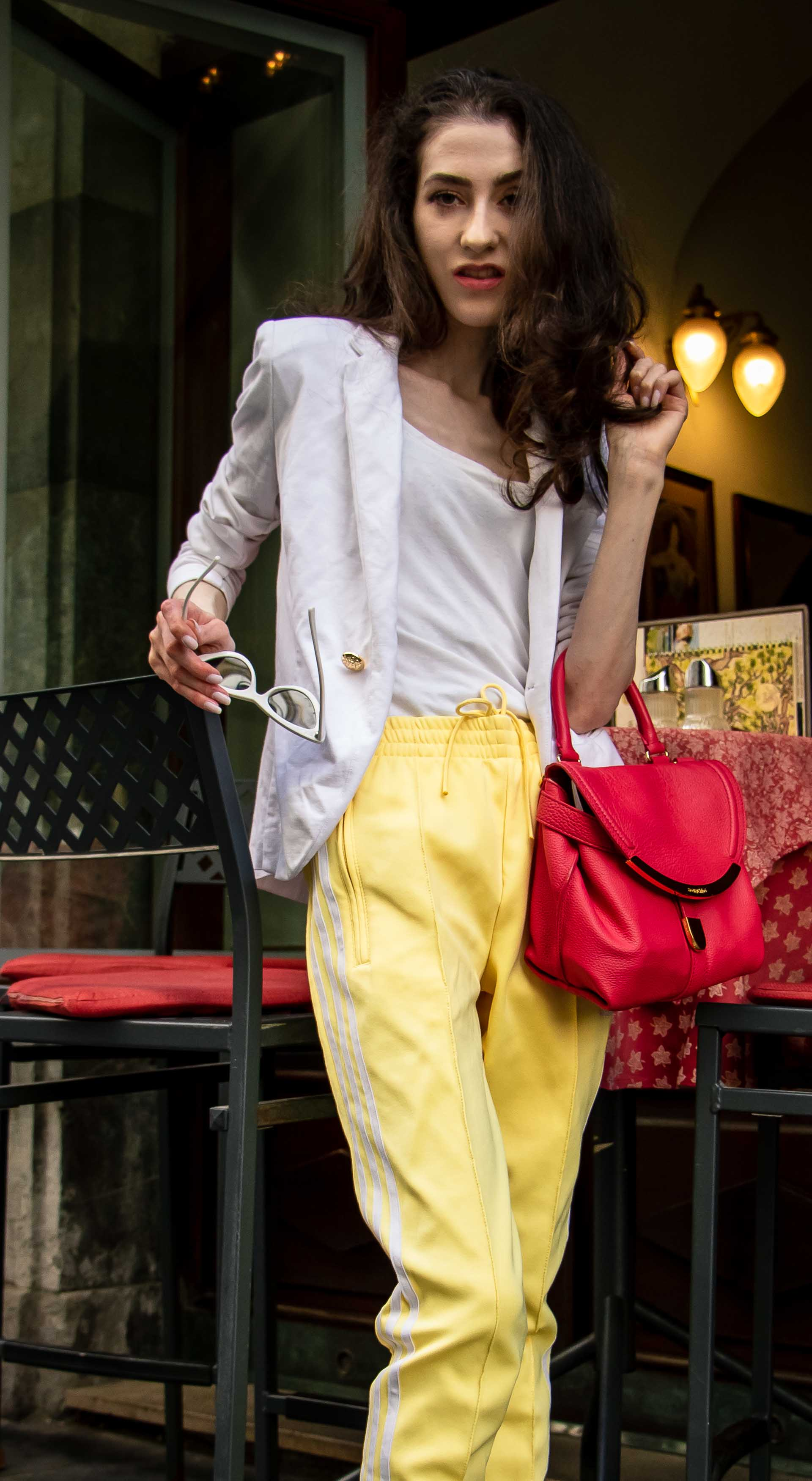 Veronika Lipar Fashion Editor of Brunette from Wall Street wearing chic casual white blazer, white H&M t-shirt, yellow Addidas track pants, See by Chloé pink top handle bag, Adam Selman x Le Specs white cat eye Lolita sunglasses, pink blush Gianvito Rossi plexi pumps sitting on bar stool on the street