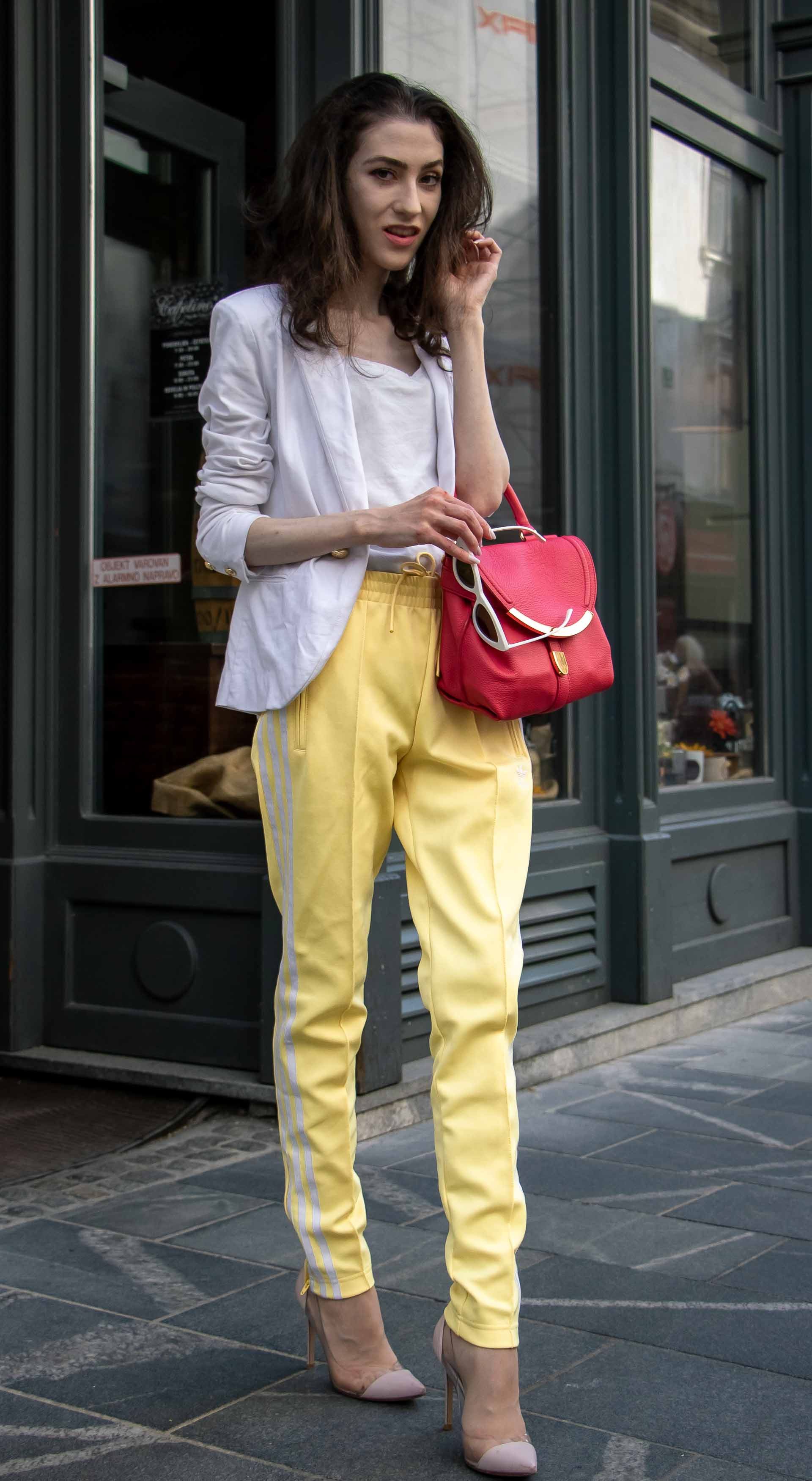 Veronika Lipar Fashion Blogger of Brunette from Wall Street wearing white blazer, white H&M t-shirt, yellow Addidas track pants, See by Chloé pink top handle bag, Adam Selman x Le Specs white cat eye Lolita sunglasses, pink blush Gianvito Rossi plexi pumps on the street in Ljubljana