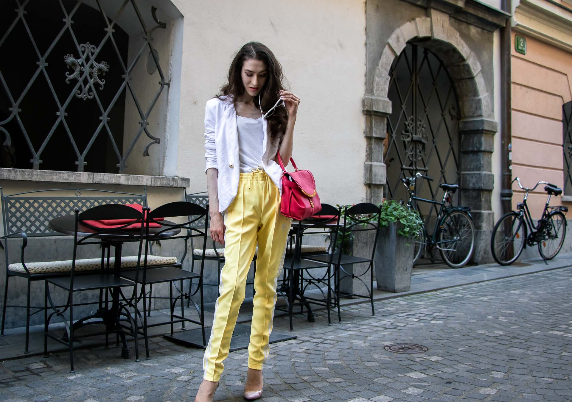 Veronika Lipar Fashion Editor of Brunette from Wall Street wearing chic casual white blazer, white H&M t-shirt, yellow Addidas track pants, See by Chloé pink top handle bag, Adam Selman x Le Specs white cat eye Lolita sunglasses, pink blush Gianvito Rossi plexi pumps on the street