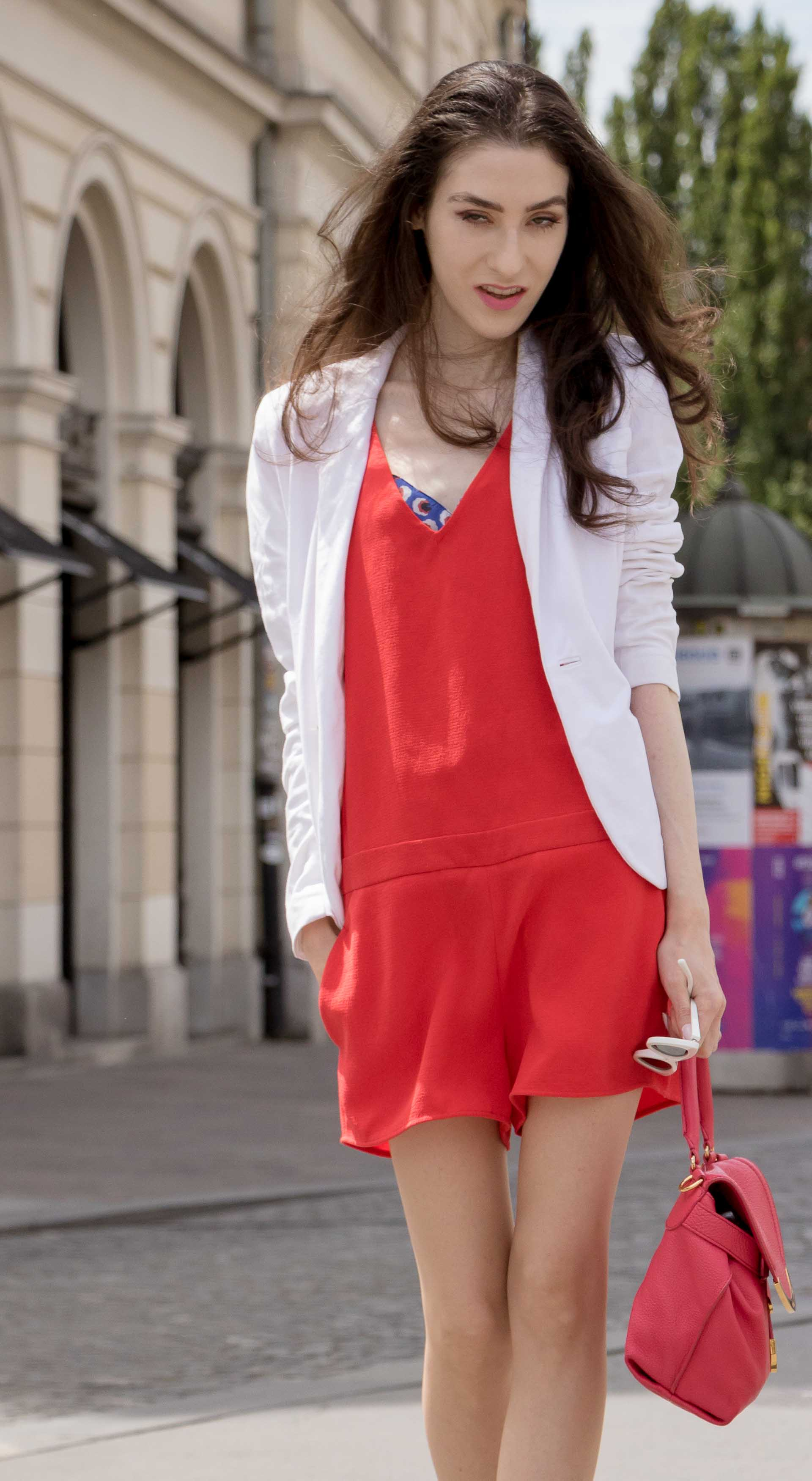 Veronika Lipar Fashion Blogger of Brunette from Wall Street wearing red playsuit, white blazer, Adam Selman x Le Specs white cat eye Lolita sunglasses, pink top handle See by Chloe bag, Gianvito Rossi plexi pumps on summer day in Ljubljana