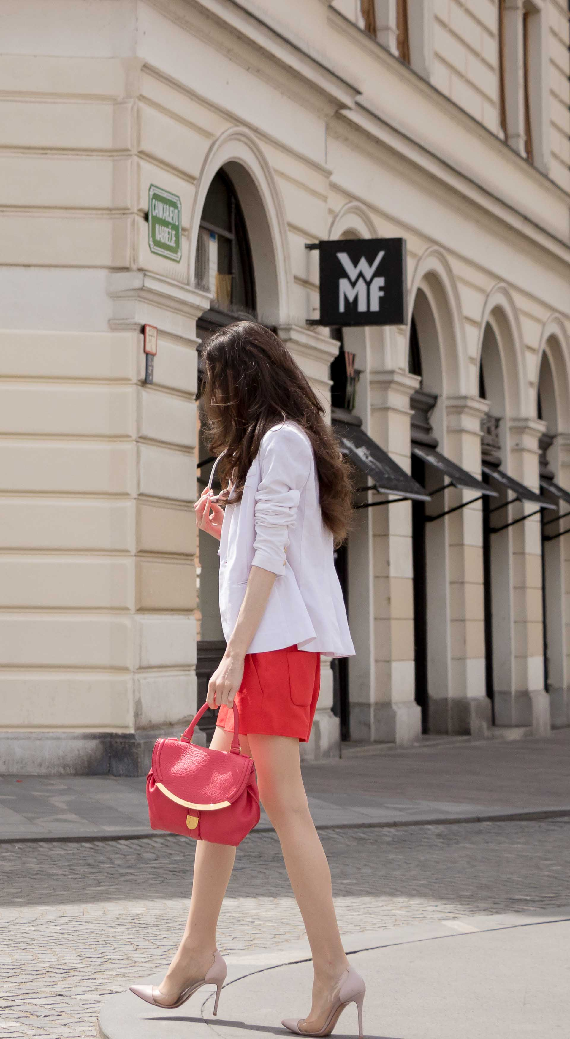 Veronika Lipar Fashion Blogger of Brunette from Wall Street dressed in red playsuit, white blazer, Adam Selman x Le Specs white cat eye Lolita sunglasses, pink top handle See by Chloe bag, Gianvito Rossi plexi pumps on summer day in Ljubljana